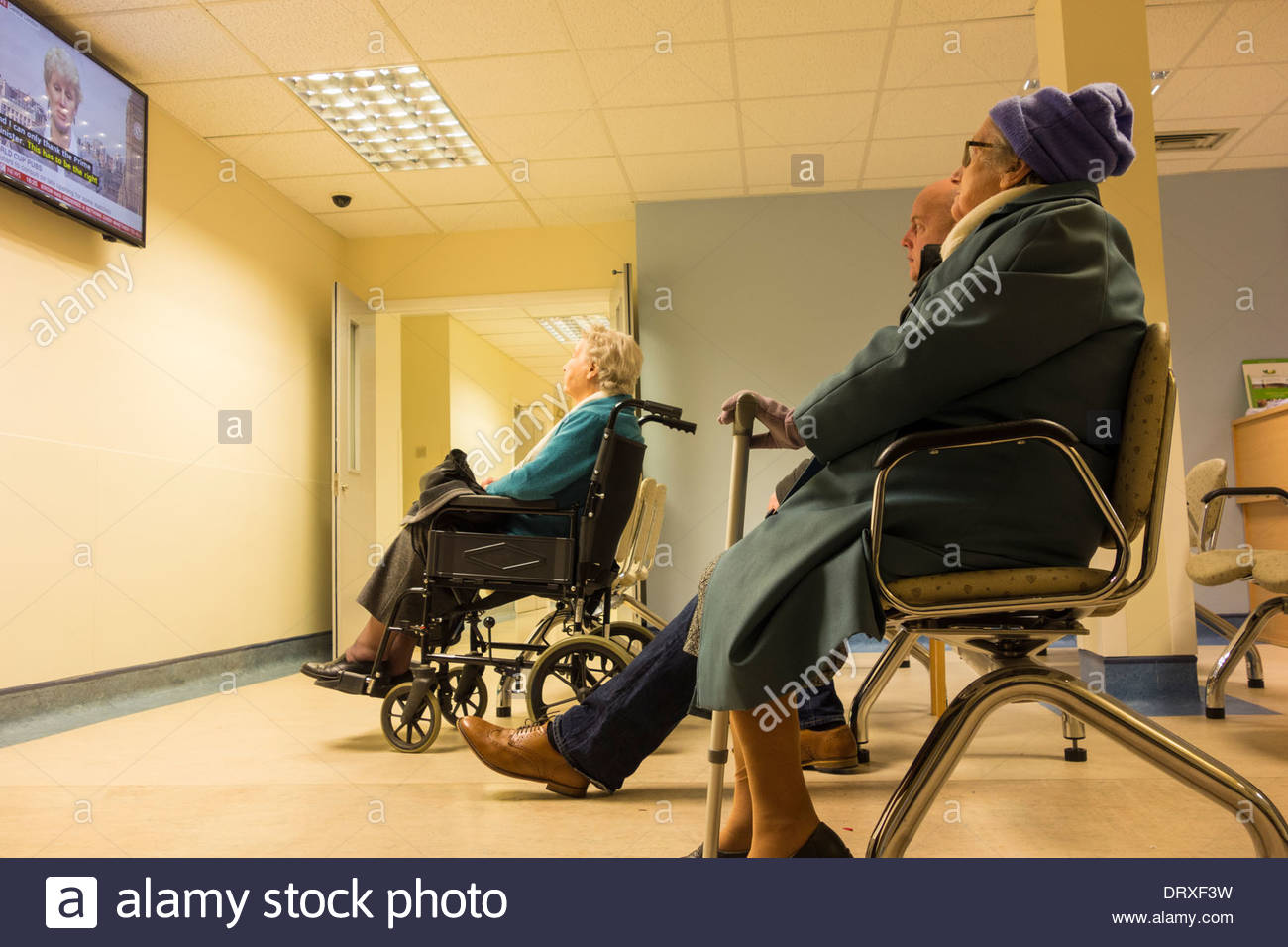 People watching TV in outpatient clinic waiting room in NHS hospital. UK - Stock Image