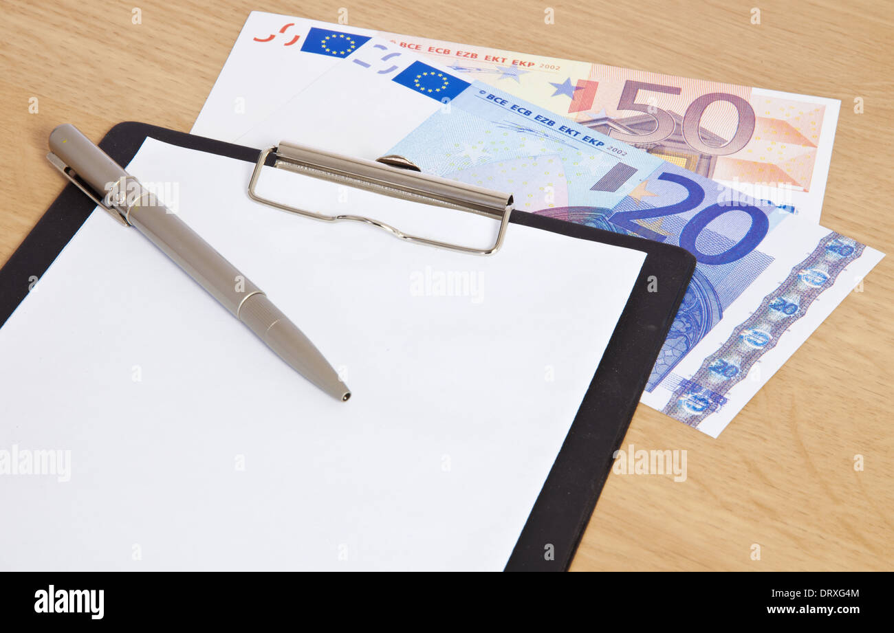 70 euro lying next to clipboard. - Stock Image