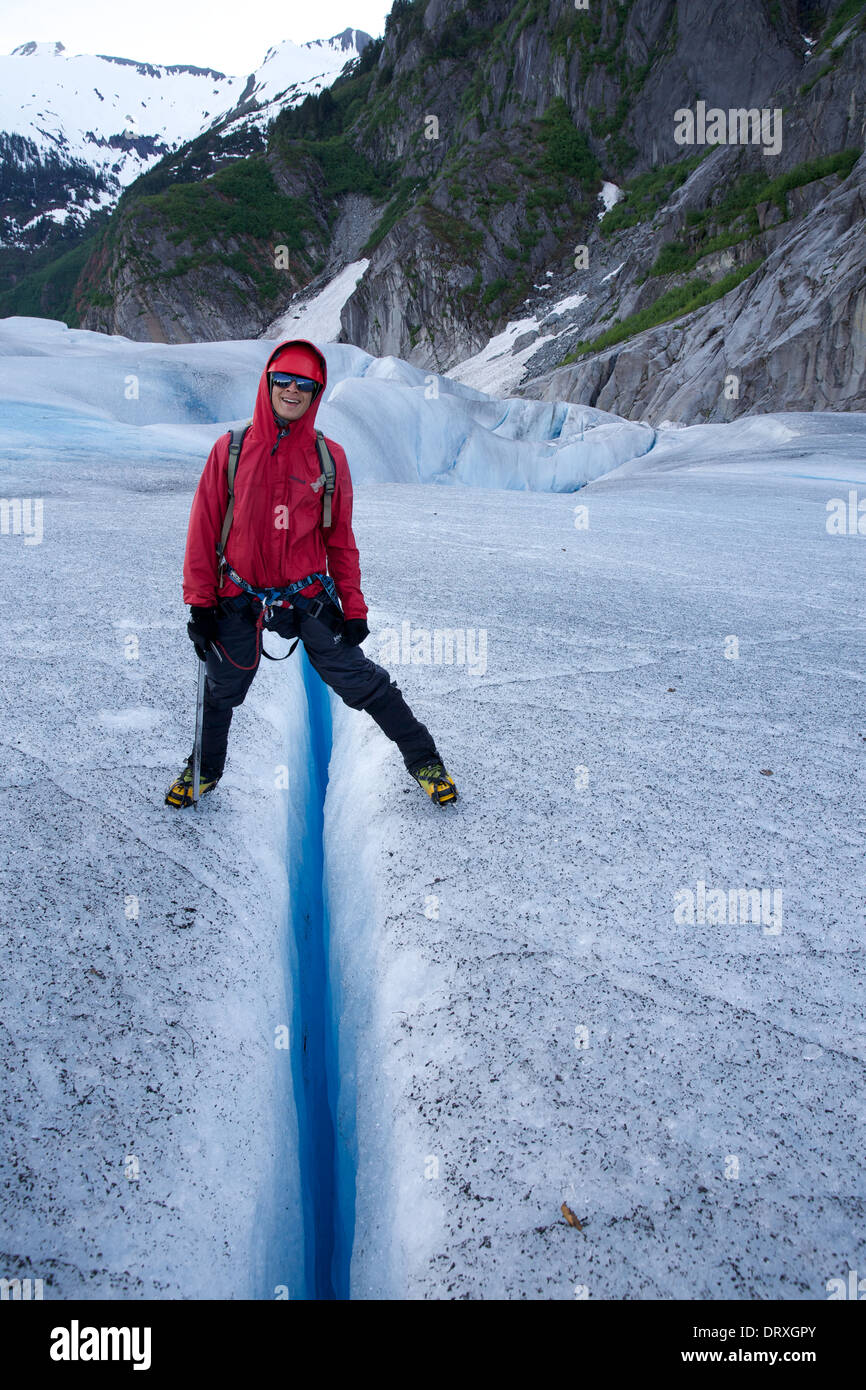 A person stamps across a crevasse on the Mendenhall Glacier, Juneau, Alaska - Stock Image
