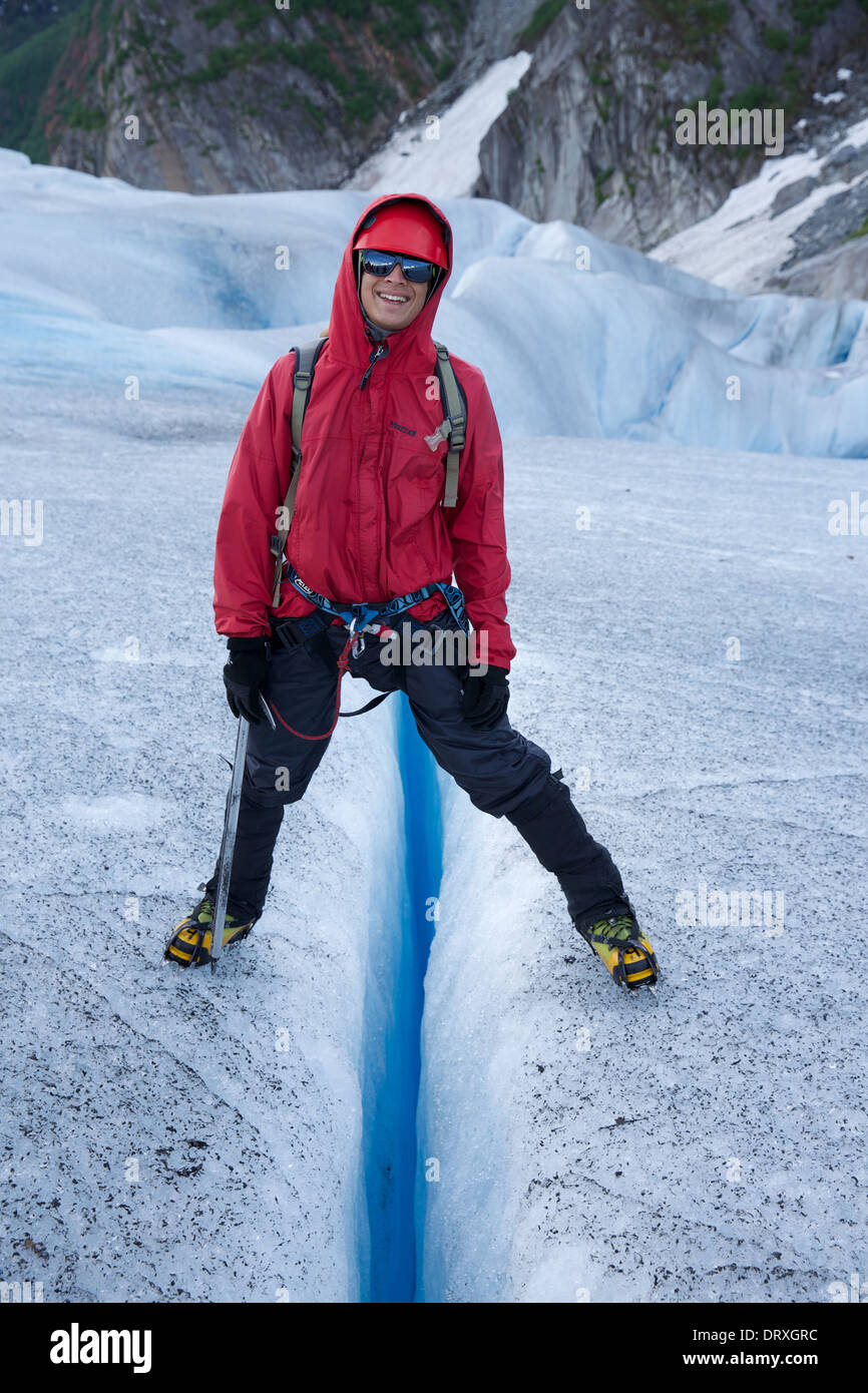 A person stands across a crevasse in the Mendenhall Glacier, near Juneau, Alaska - Stock Image