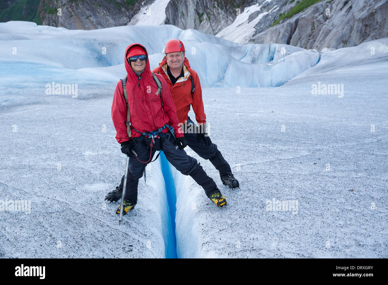 Two people stand across a crevasse in the Mendenhall Glacier, Juneau, Alaska - Stock Image