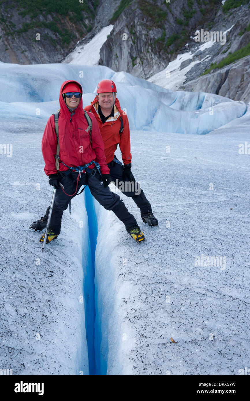 Two people standing across a crevasse in the Mendenhall Glacier, Alaska - Stock Image