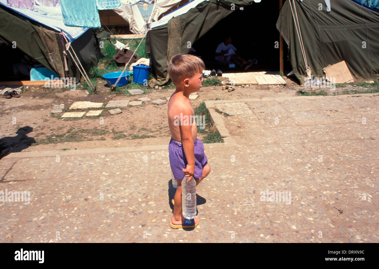 Child carrying water in swimming pool refugee camp in Tirana Albania for Kosovar refugees that fled the Kosovan Stock Photo