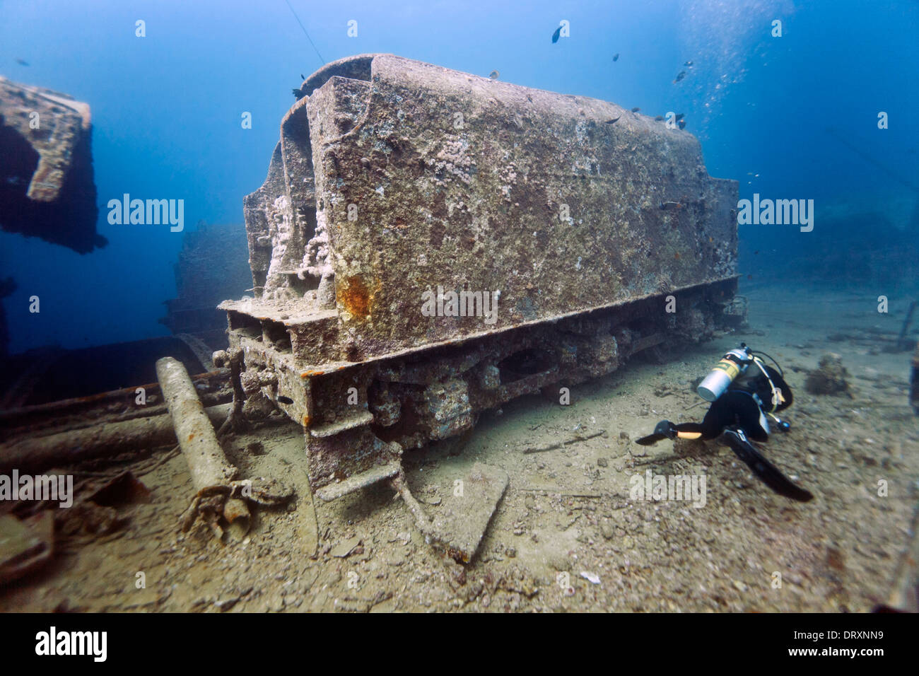 A scuba diver passes a coal tender on the wreck of the SS Thislegorm, Red Sea, Egypt - Stock Image