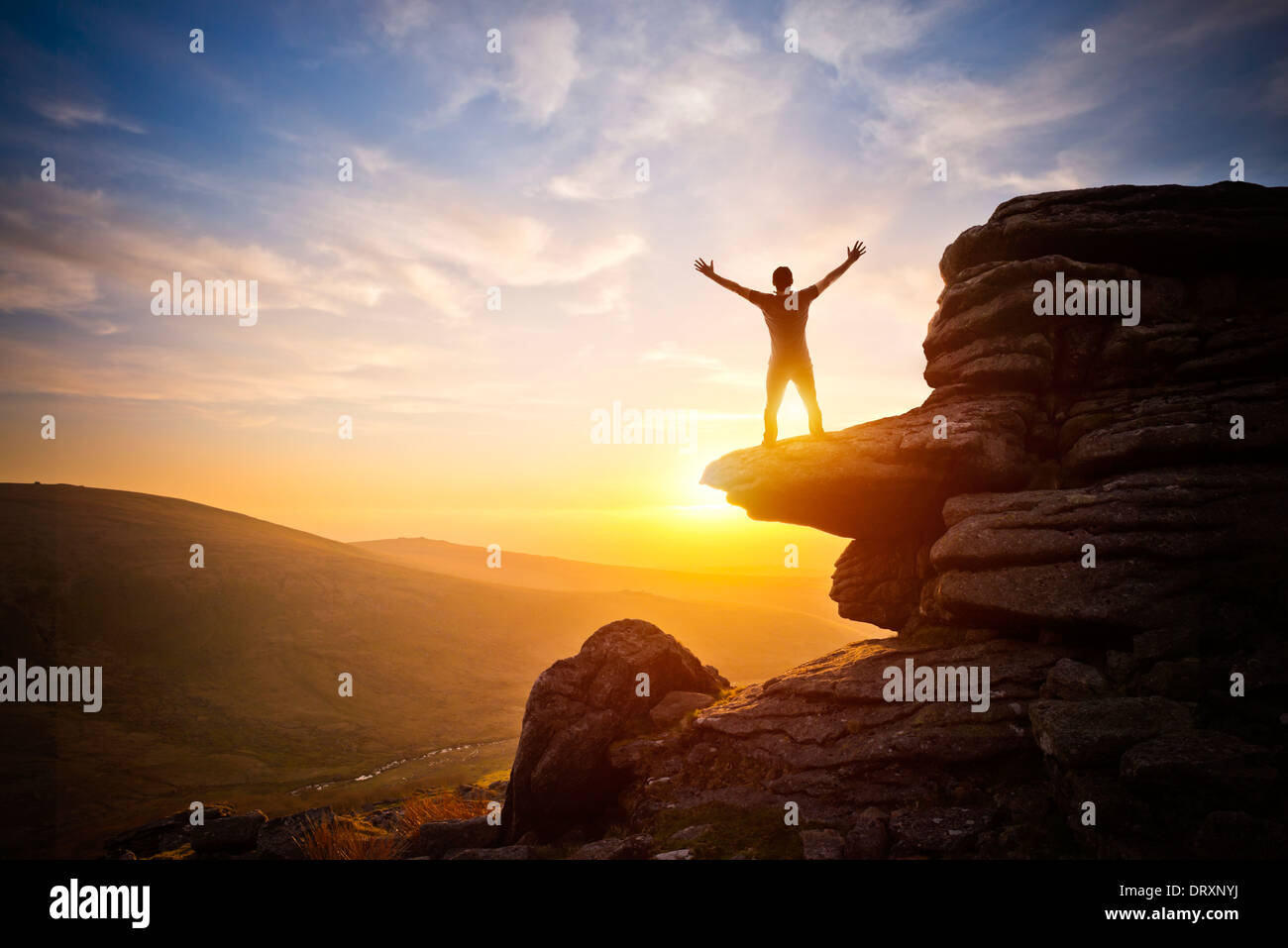 A person expressing freedom - reaching up into the sky against a sunset. - Stock Image