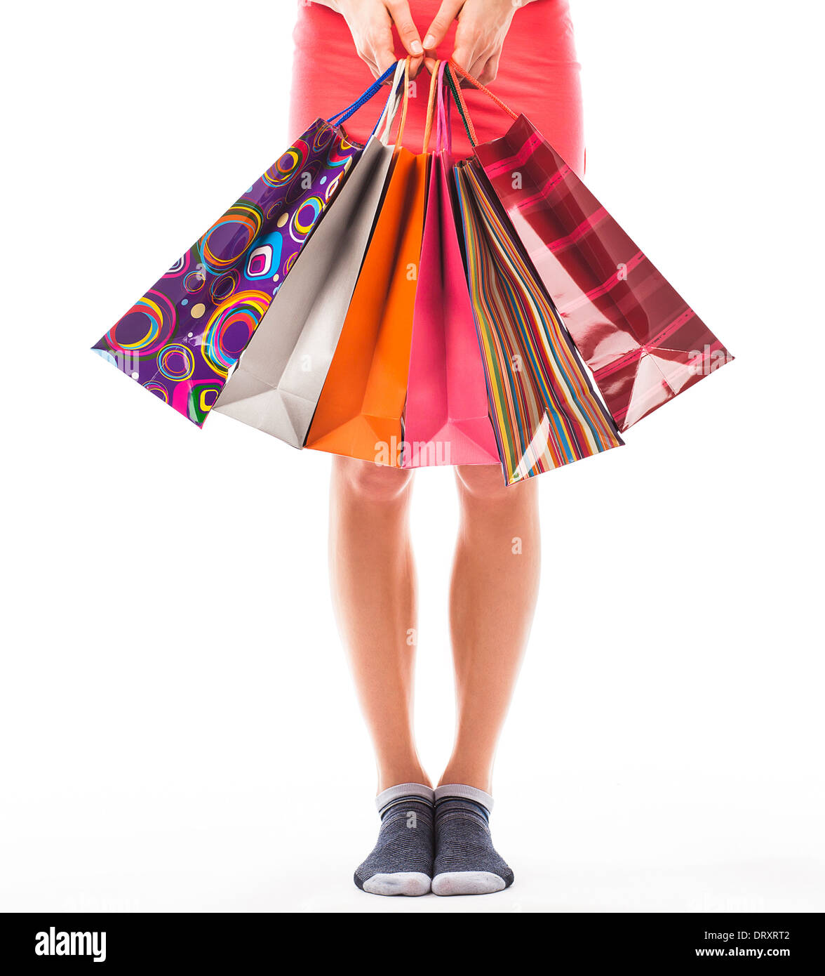 Young woman holding shopping bags, view of her lower body - Stock Image