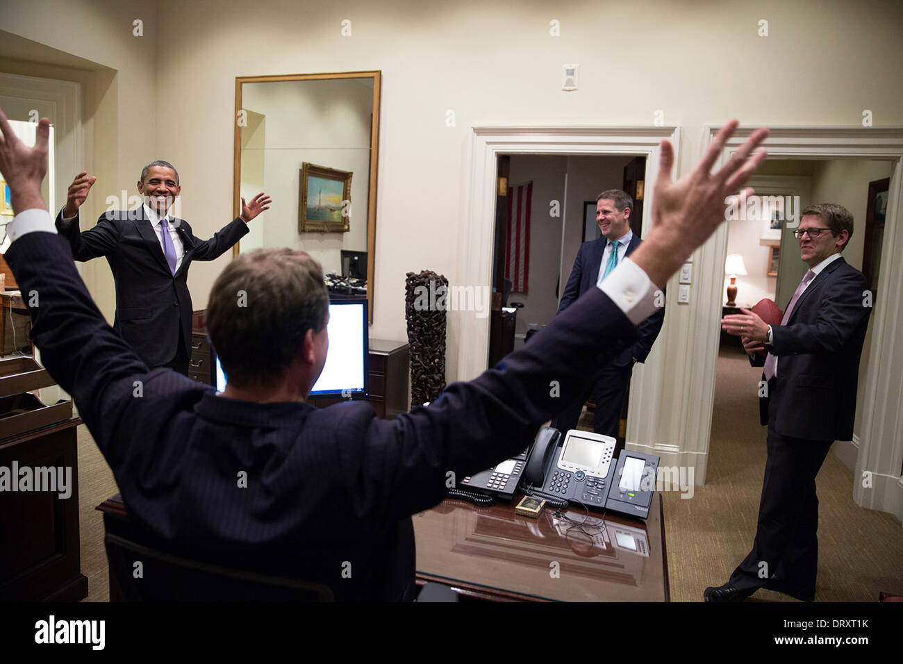 US President Barack Obama celebrates with Press Secretary Jay Carney in the Outer Oval Office following the Senate vote on the federal government shutdown and debt ceiling October 16, 2013 in Washington, DC. Trip Director Marvin Nicholson and Senior Advisor Dan Pfeiffer watch. - Stock Image