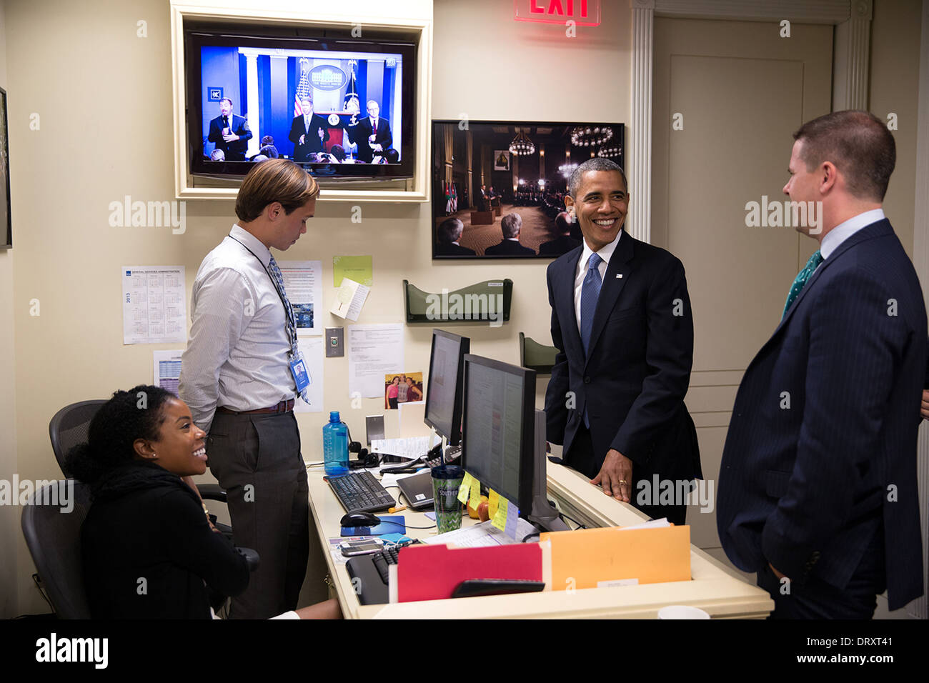 US President Barack Obama talks with Senior Advisor Dan Pfeiffer, right, and Press Assistants Desiree Barnes and Peter Velz in the Lower Press Office prior to delivering a statement regarding budget negotiations in the James S. Brady Press Briefing Room of the White House September 30, 2013 in Washington, DC. - Stock Image