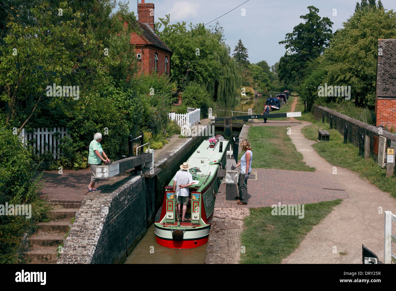 A narrowboat entering Cropredy Lock and about to go under Cropredy Lock Bridge on the Oxford Canal in Cropredy, Oxfordshire - Stock Image