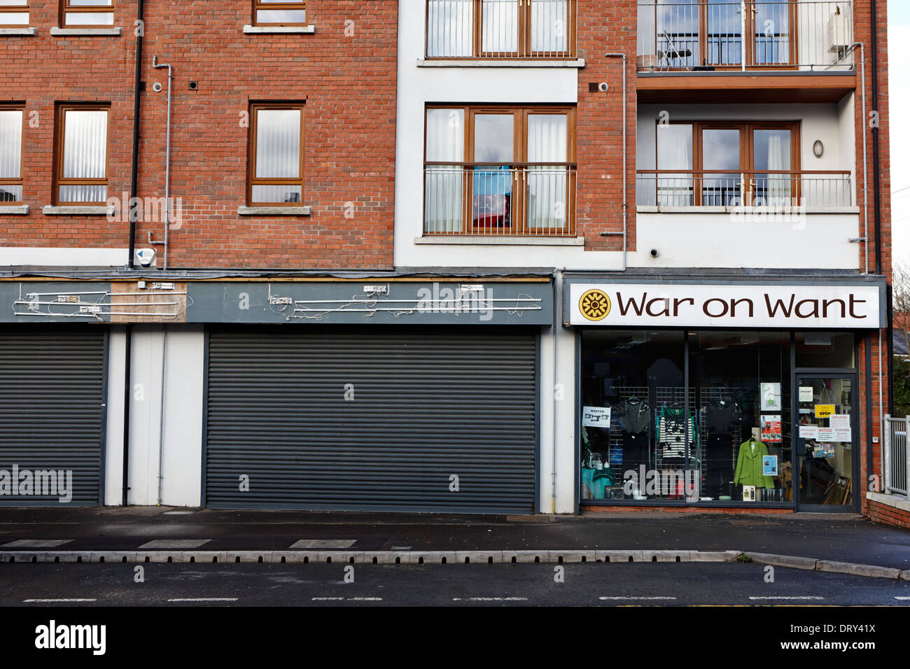 war on want charity shop next to closed shop on high street dunmurry belfast uk - Stock Image