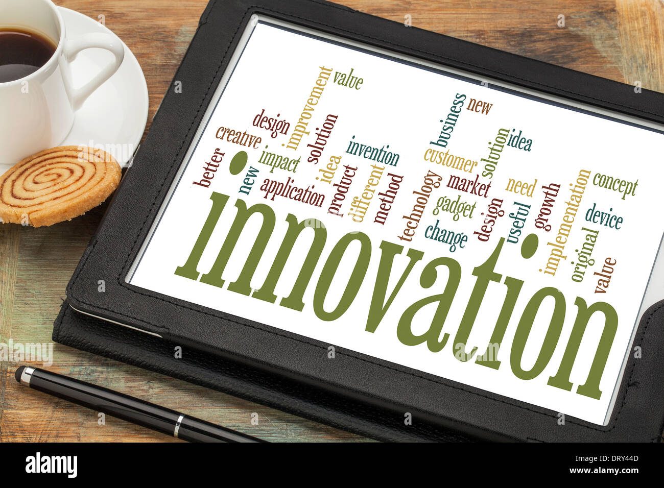 innovation concept - word cloud on a digital tablet with a cup of coffee - Stock Image