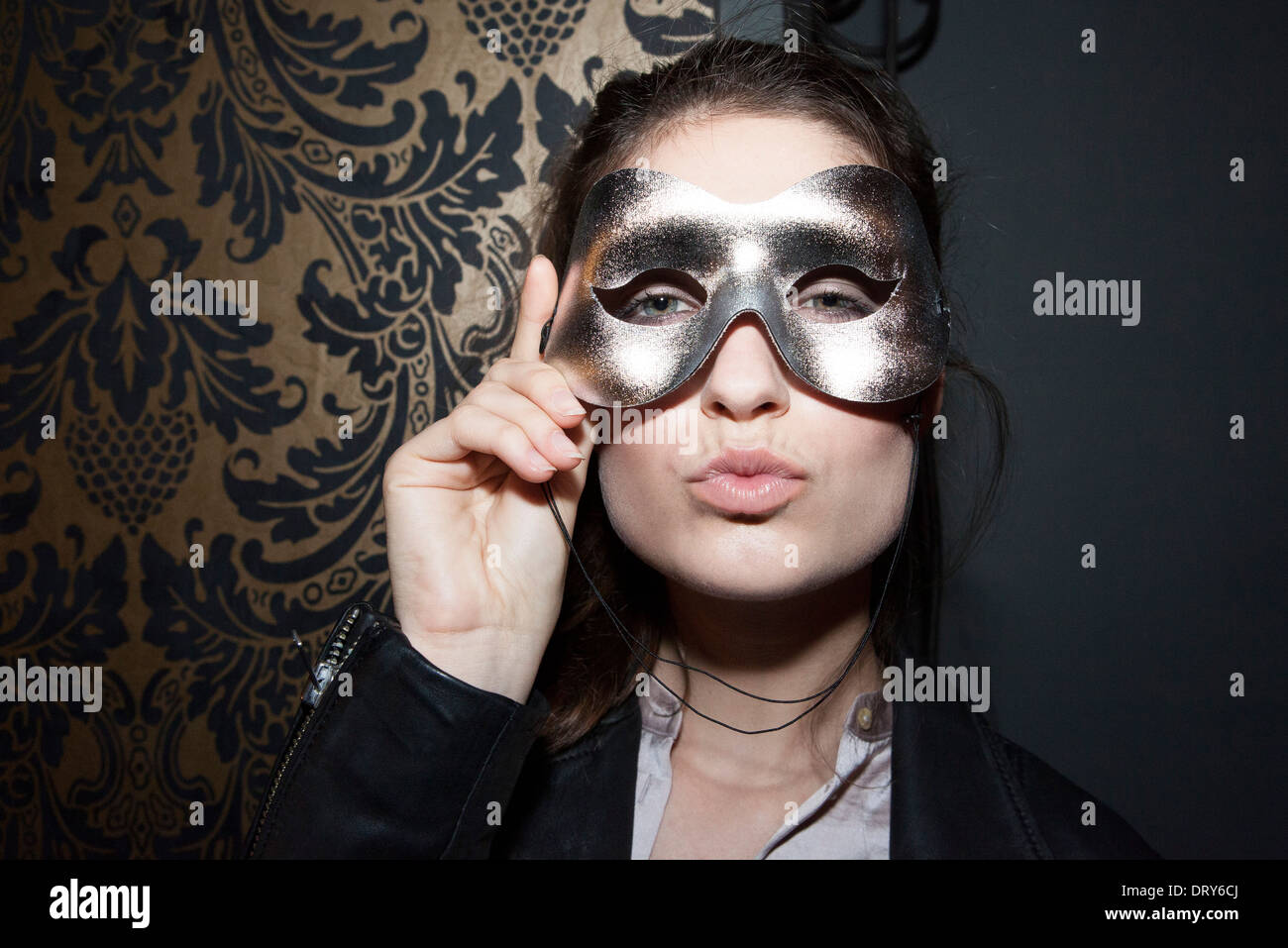 Woman wearing party mask, pursing lips, portrait - Stock Image
