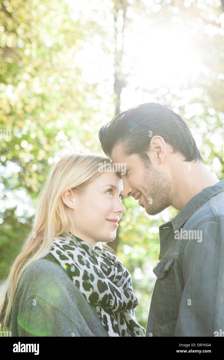Couple nuzzling each other outdoors - Stock Image