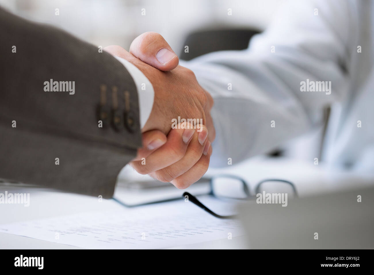 Business deal closed with handshake - Stock Image