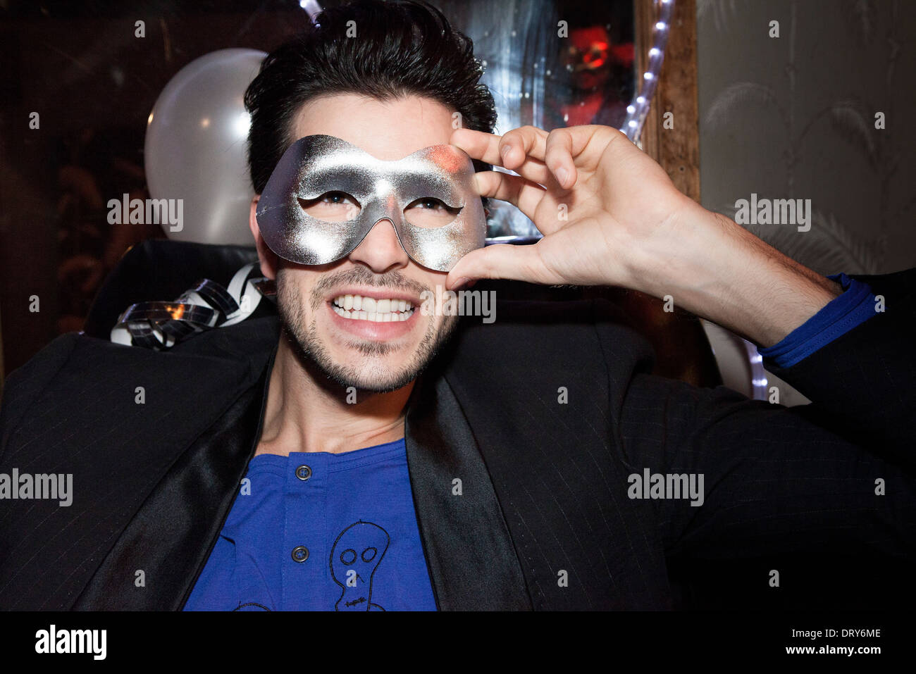 Man wearing party mask, portrait - Stock Image