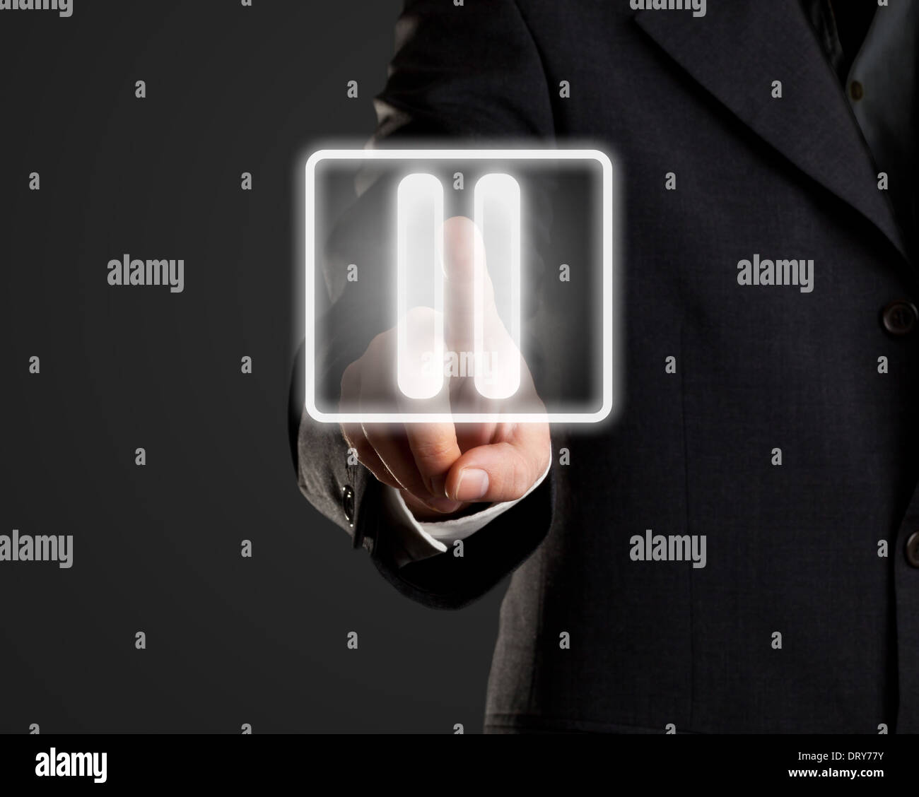 Businessman pressing pause button on virtual screen - Stock Image
