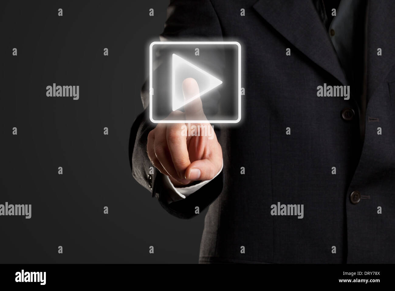 Businessman pressing start/ play button on virtual screen - Stock Image