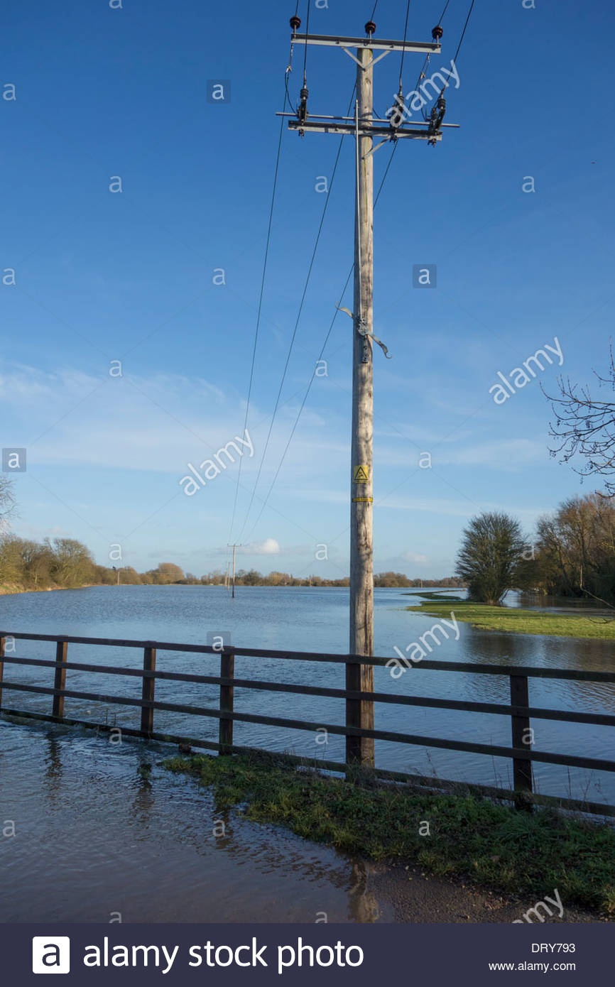 Electricity pylon above the flooded flood plain of the River Great Ouse as the river breaks its banks - Stock Image