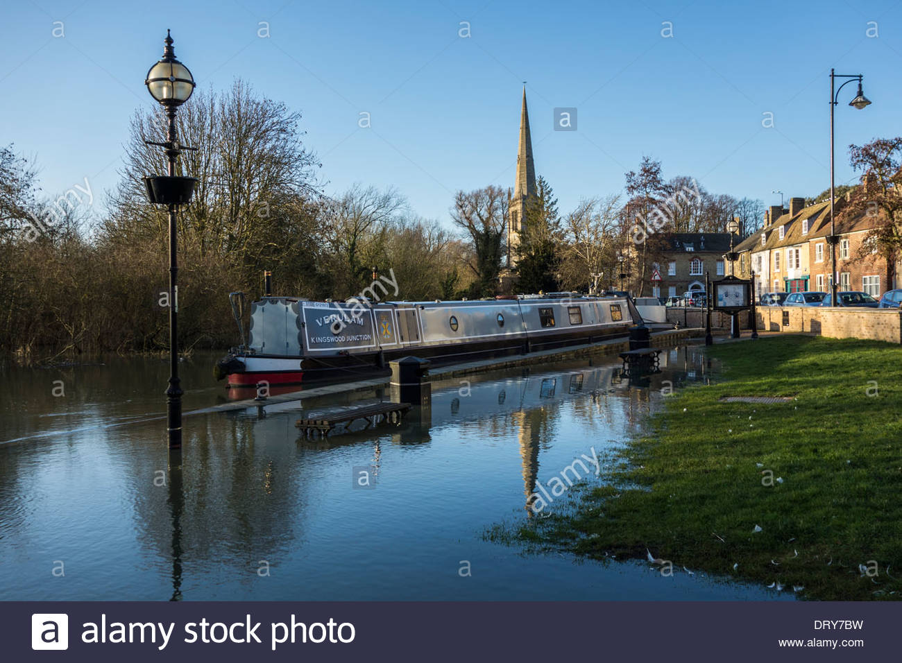 A narrowboat moored at St Ives, Cambridgeshire, surrounded by floodwater - Stock Image