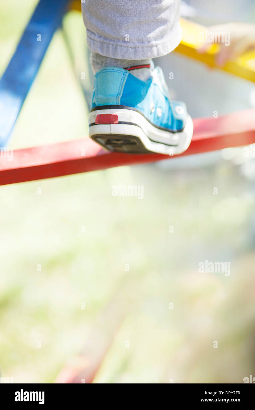 Child climbing on jungle gym, low section - Stock Image