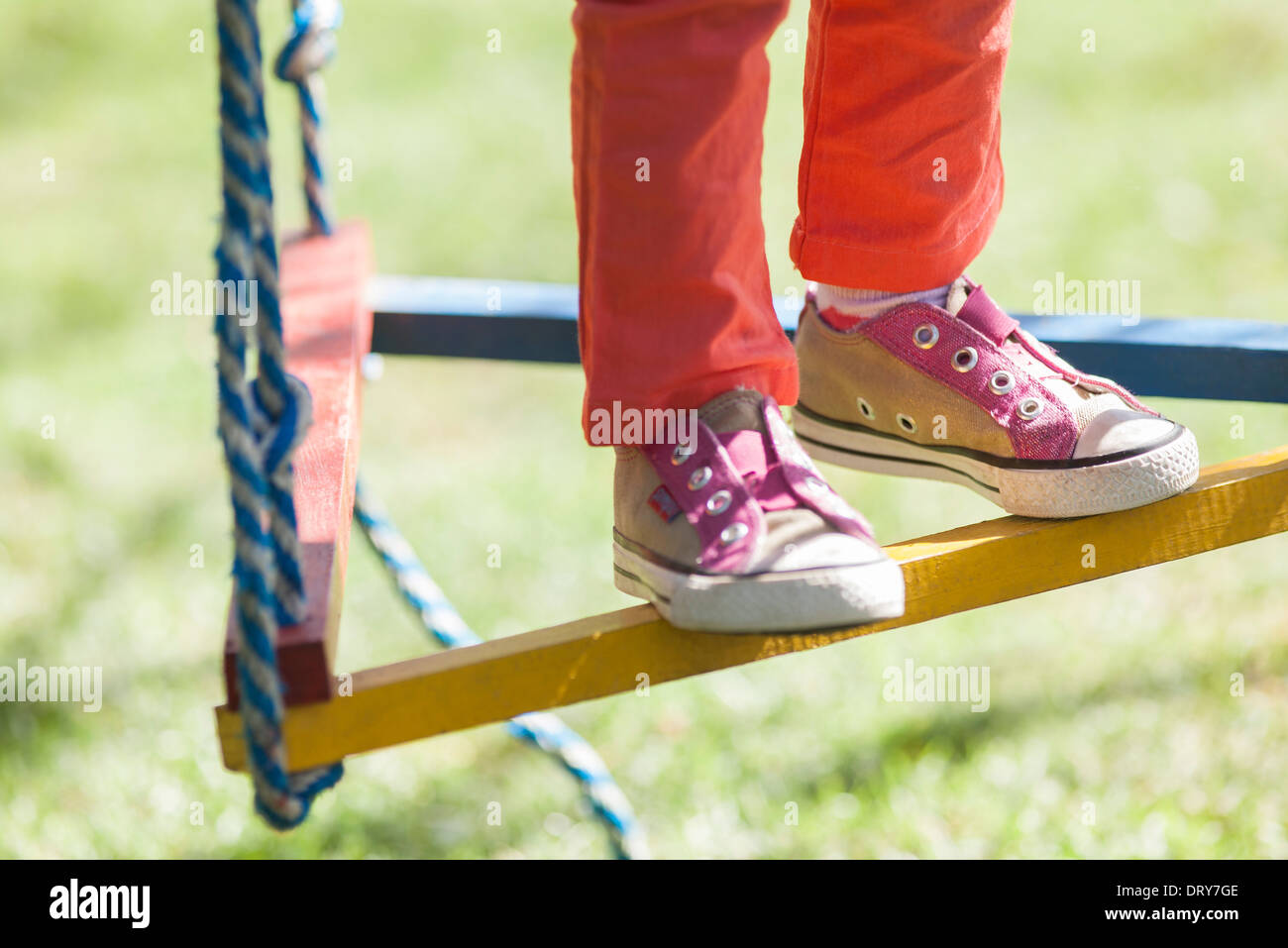 Child standing on swing, low section - Stock Image