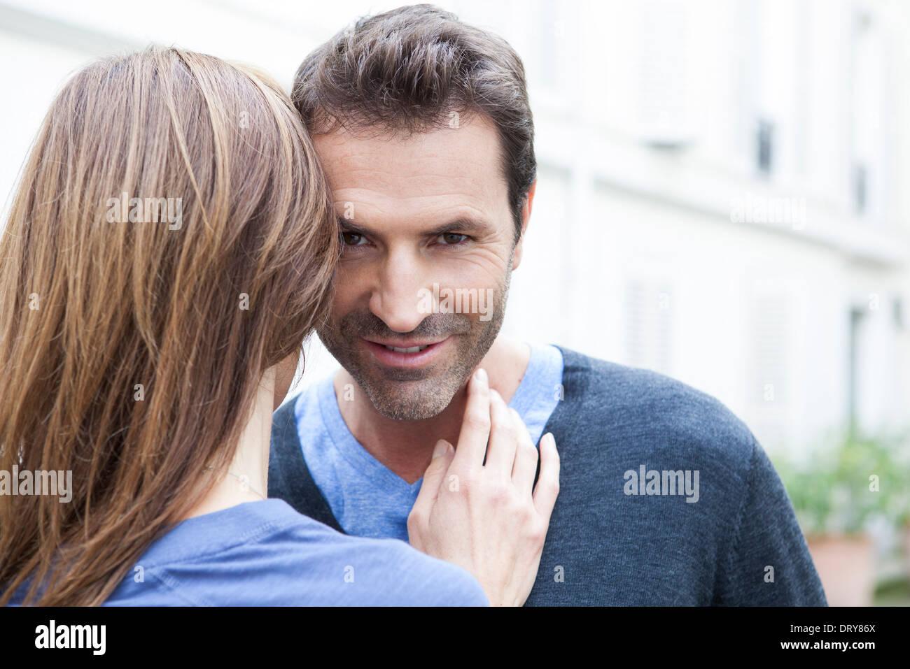 Couple embracing, man looking at camera - Stock Image