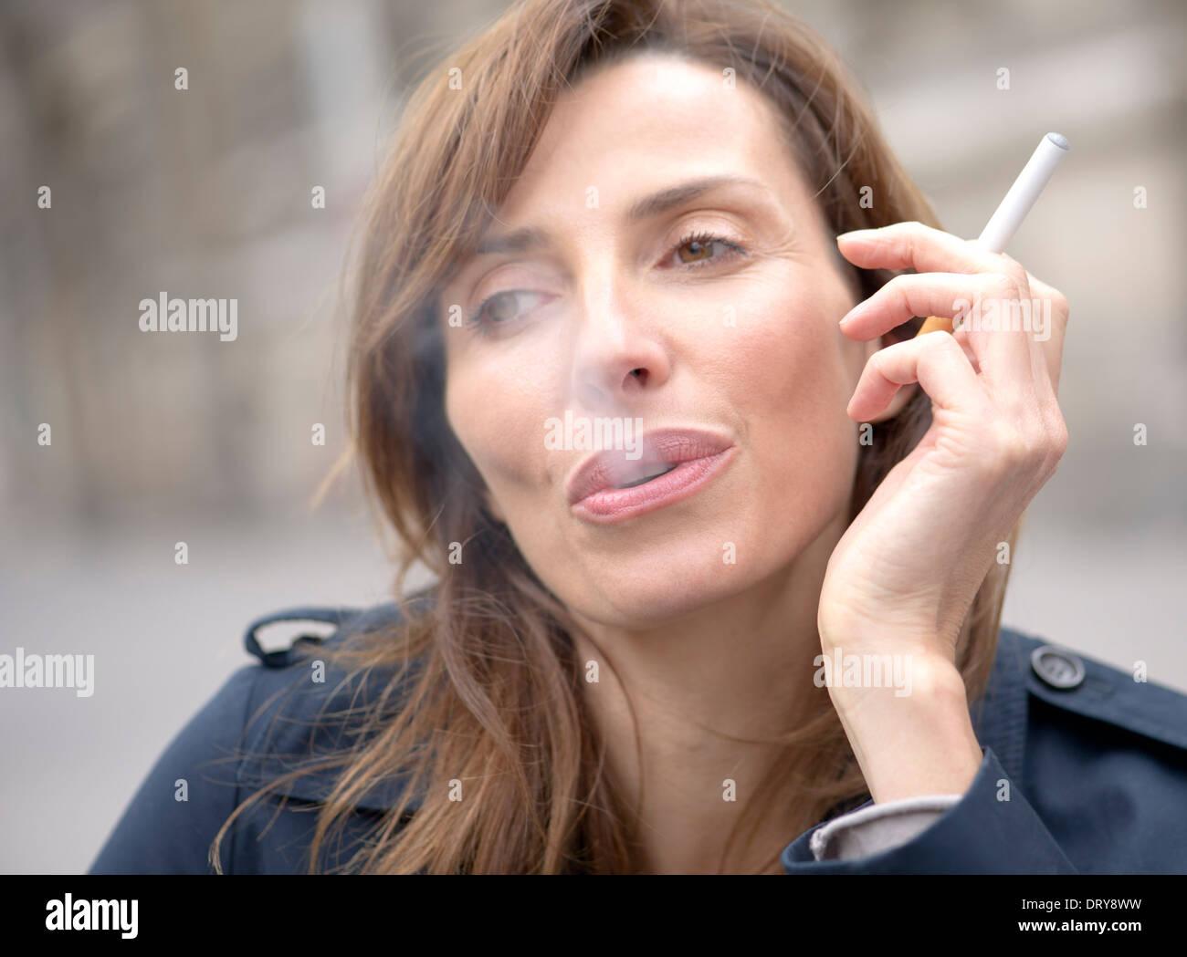 Woman smoking electronic cigarette - Stock Image