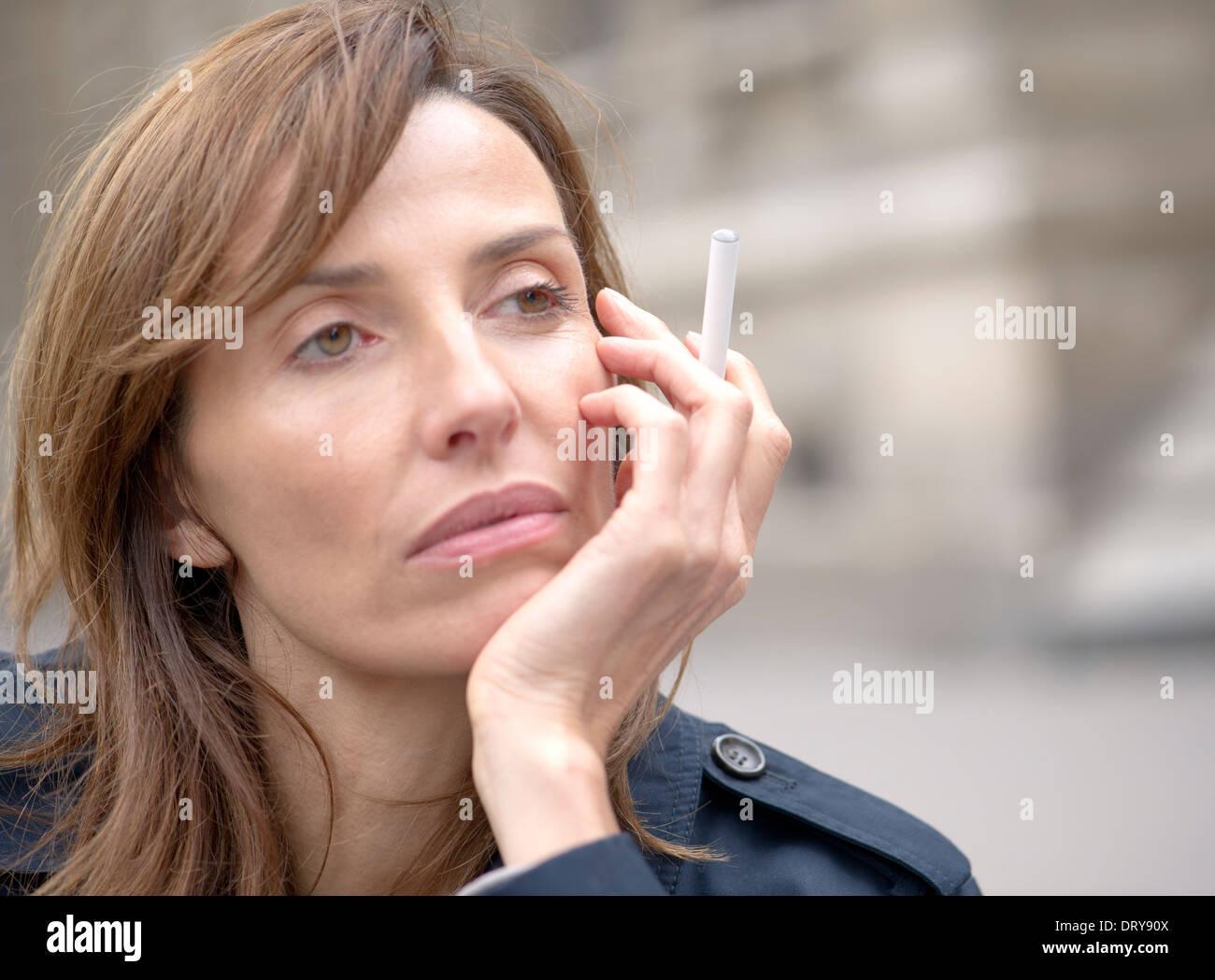 Woman smoking electronic cigarette outdoors - Stock Image