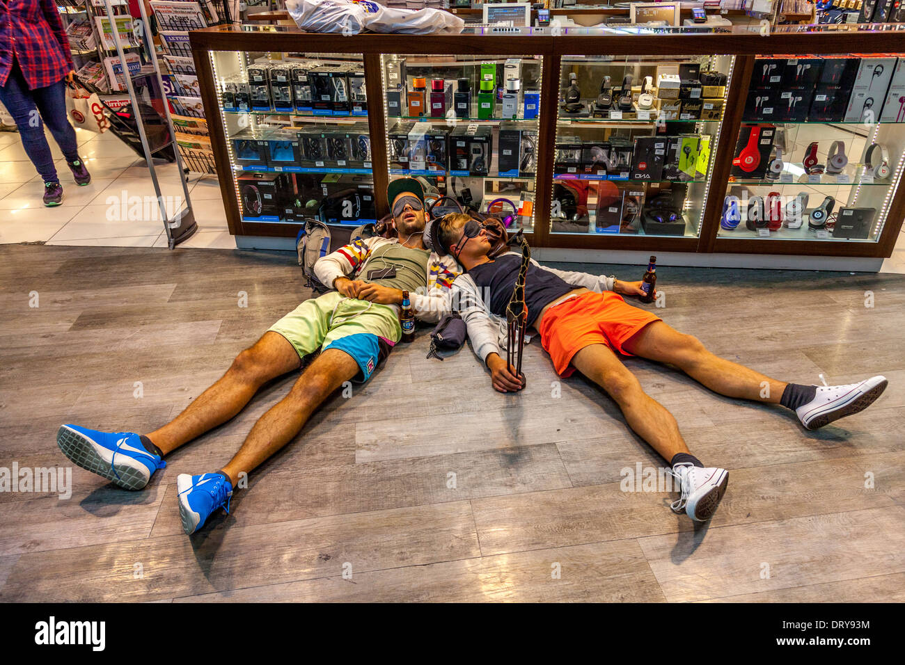 Two Sleeping Travellers Outside The Duty Free Shop, Ataturk Airport, Istanbul, Turkey - Stock Image
