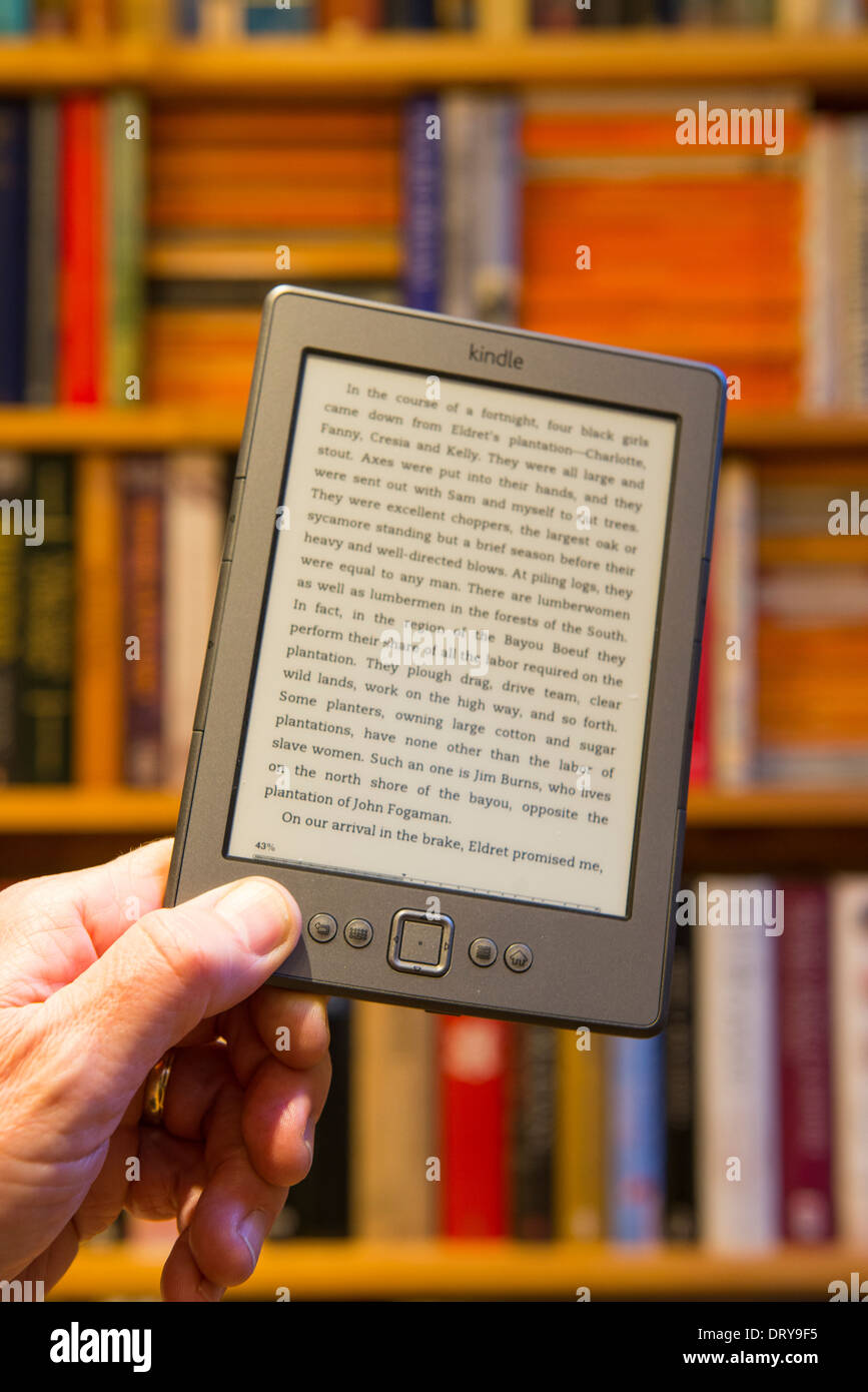 Holding An Amazon Kindle In Front Of A Bookshelf Stock Photo