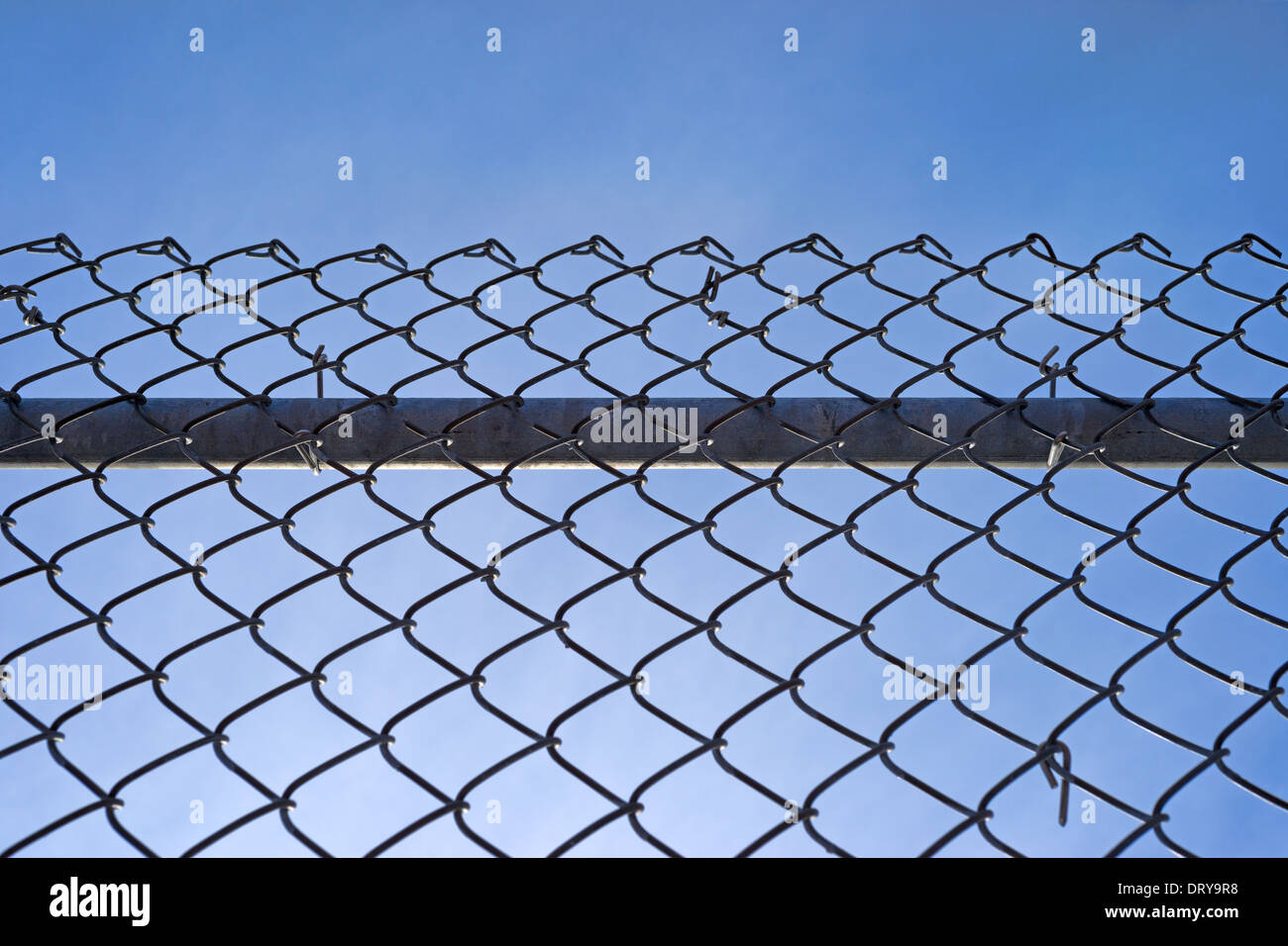 A chain link fence with a sturdy bar behind the mesh and fastenings against a blue sky with wispy clouds. - Stock Image