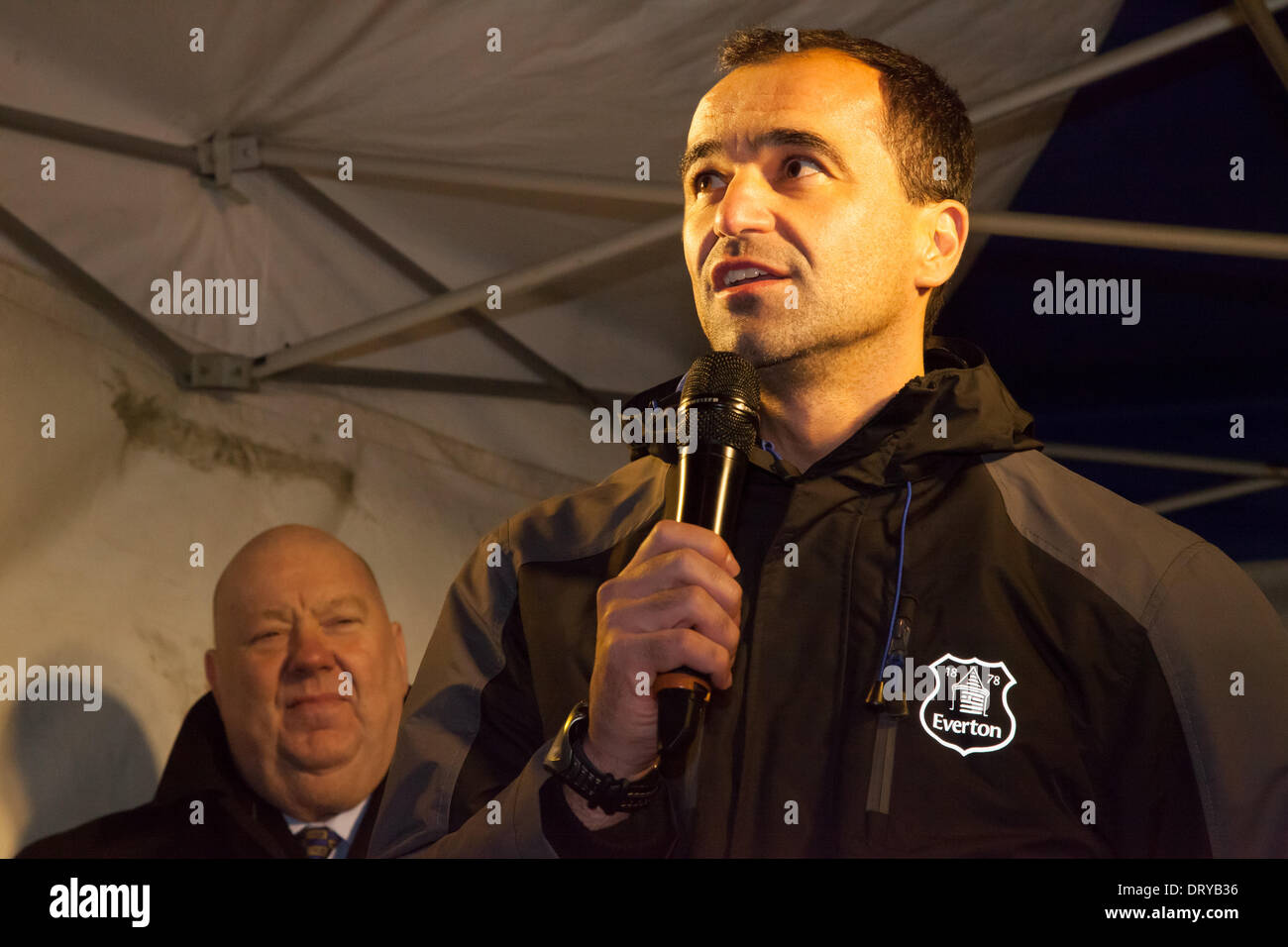 Liverpool, UK. 4th February 2014. Liverpool Mayor Joe Anderson watches as Everton manager Roberto Martinez gives a speech during a switch on ceremony in Everton. Liverpool's mayor and the Everton boss were in Browside Gardens to turn on a new projection of Everton's crest. Credit:  Adam Vaughan/Alamy Live News - Stock Image