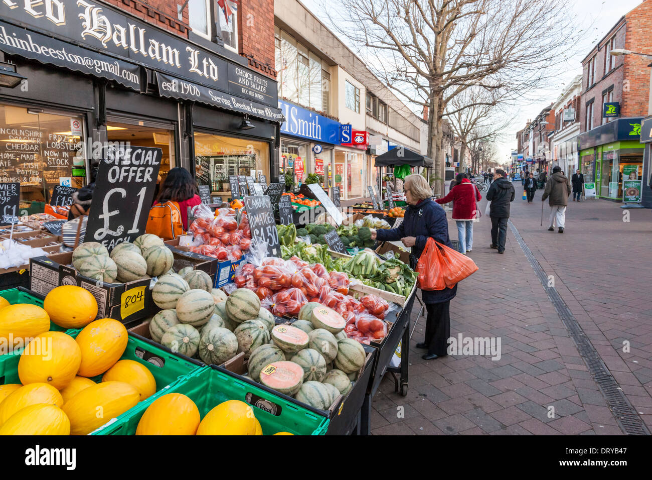 Person shopping for fruit and veg at a greengrocers among other shops in a pedestrianised area, High Street, Beeston, Nottinghamshire, England, UK - Stock Image