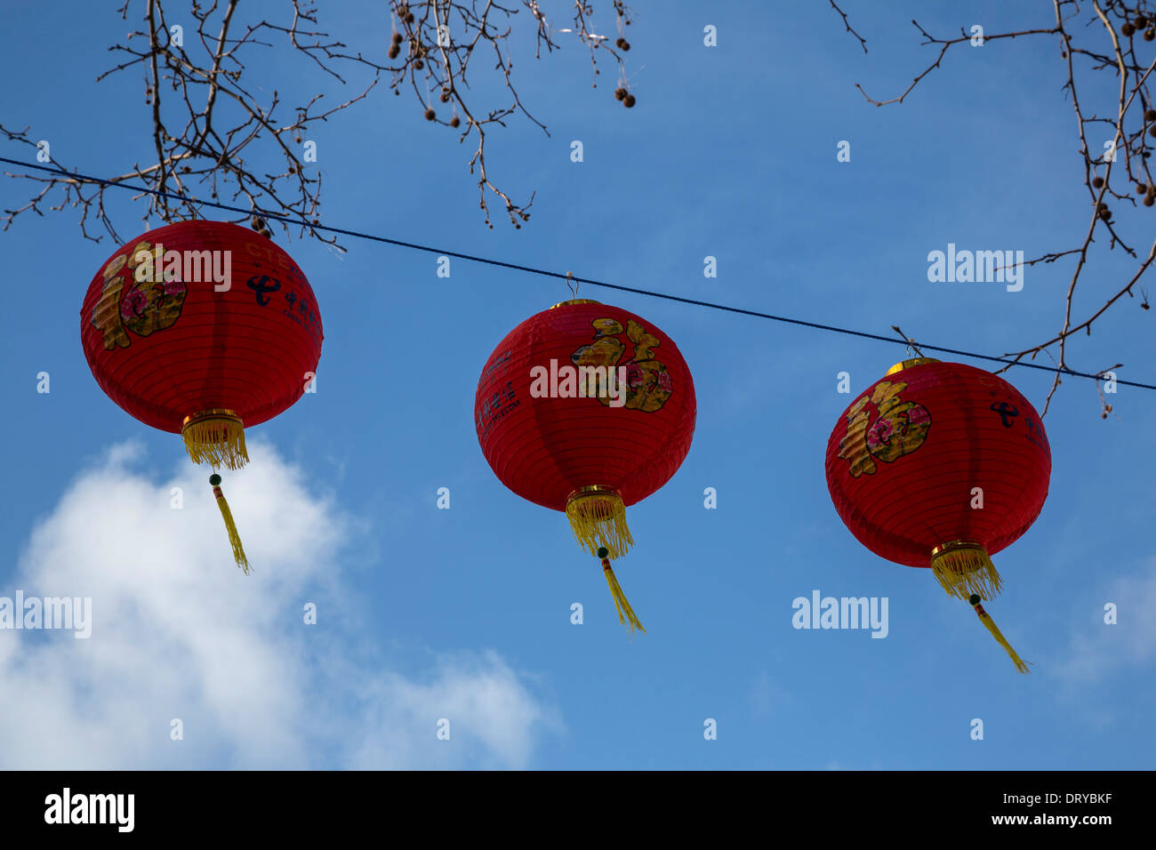 Three red Chinese lanterns against a vivid blue sky Celebrating Chinese New Year. - Stock Image