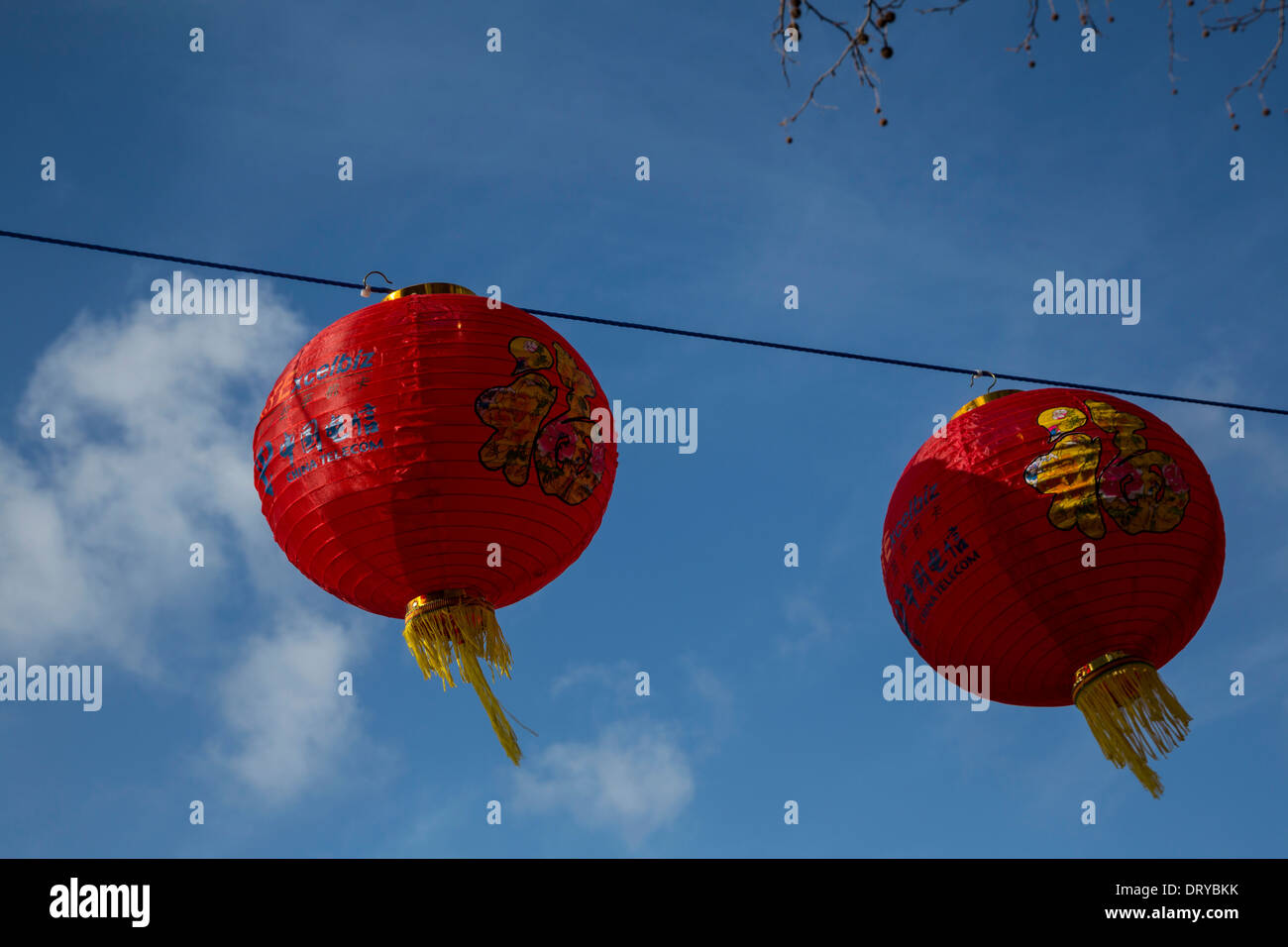 Two red Chinese lanterns against a vivid blue sky. - Stock Image