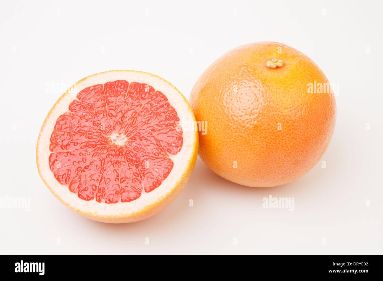Sliced ruby red grapefruit on white background - Stock Image