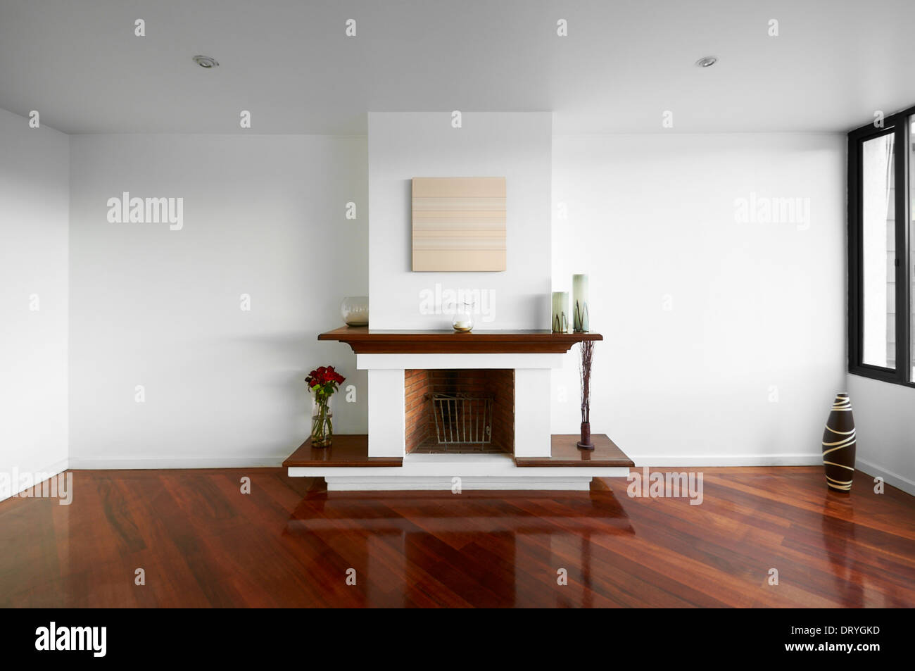 Big empty living room with a chimney, white wall and wooden floor ...