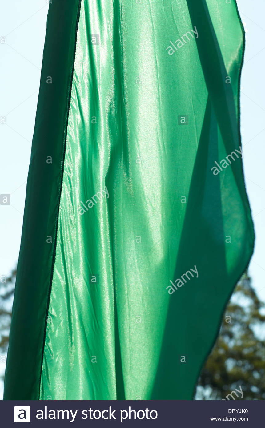Sun shines through a green silk / synthetic flag, at a school 'greenday' fair; one of the school's positive annual actions, addressing climate change. - Stock Image