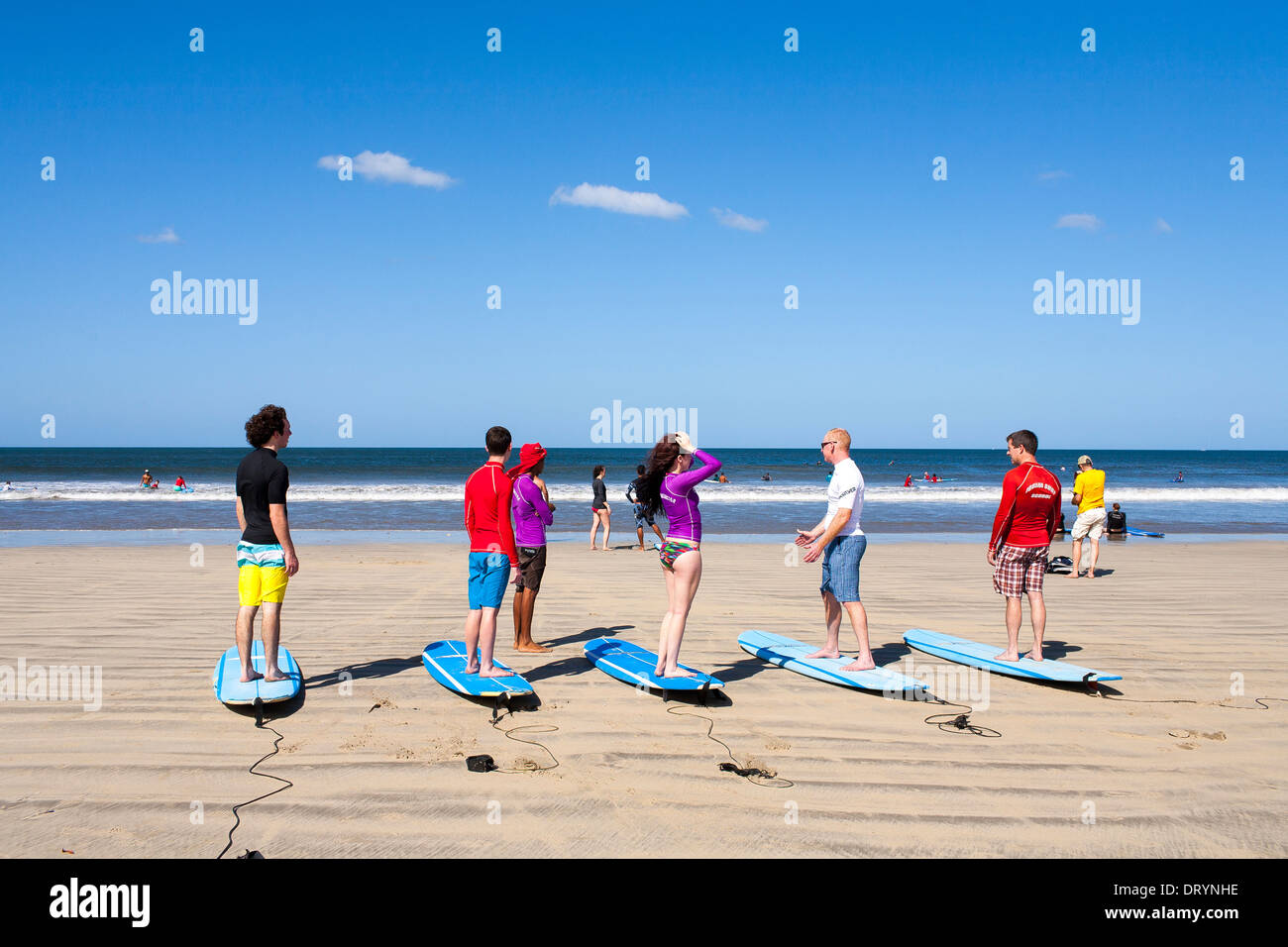 Surfers learn to surf on the beach ready for a surf lesson at a surf school on the beach of Playa Tamarindo in Guanacaste. - Stock Image