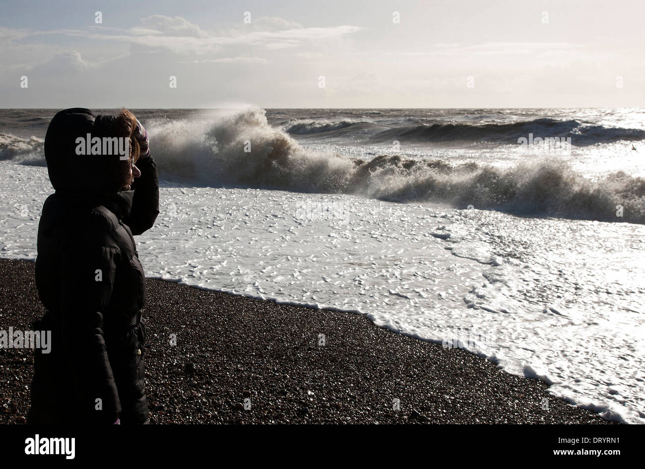 Lady on beach watching high tide storm waves Stock Photo