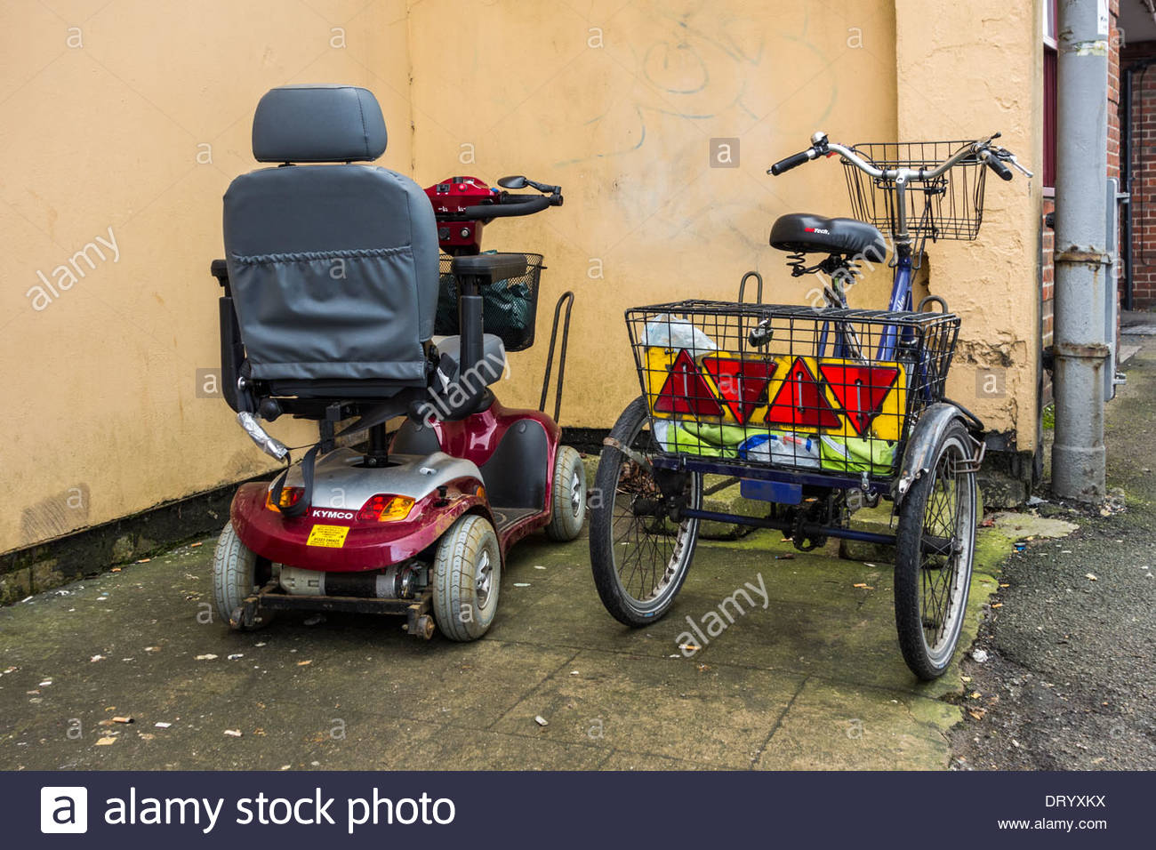 Mobility scooter and tricycle parked next to each other - Stock Image