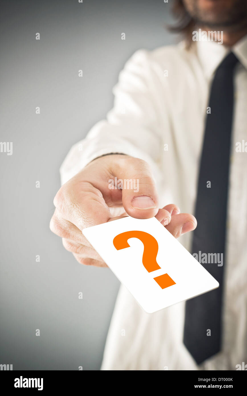 Businessman holding card with printed question mark. business poll concept. - Stock Image