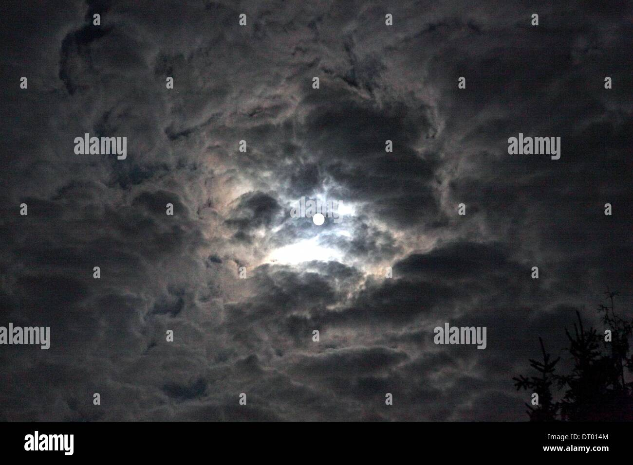 Full moon shining through clouds, Germany, Apr. 16, 2011. - Stock Image