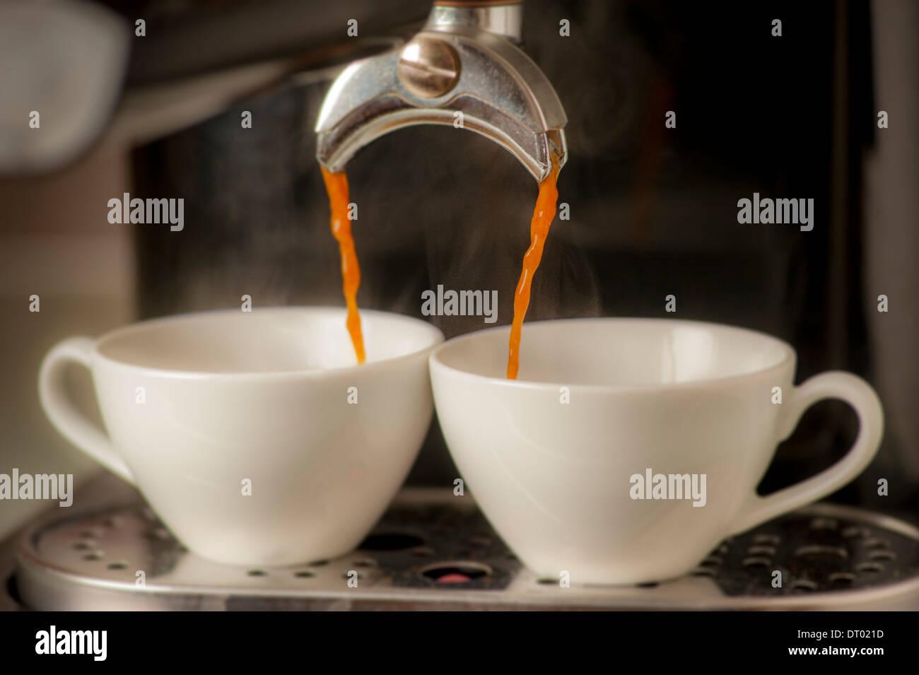 Espresso coffee machine dispensing into cups. - Stock Image