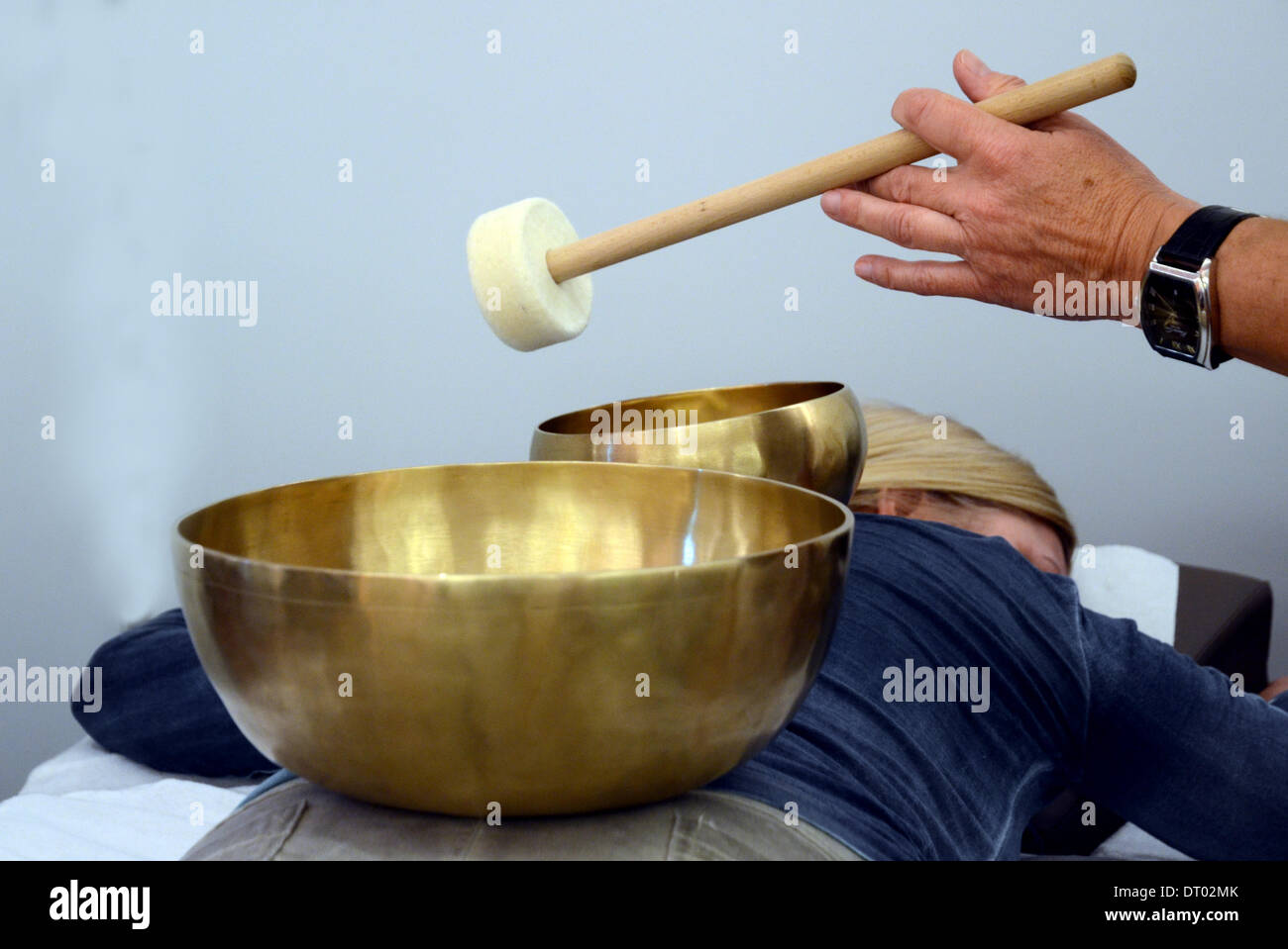 Bronze sound bowls, which are used for sound therapy and sound massages, are standing on the back of a woman at the Lifetime-Beauty Fair in Dusseldorf, North Rhine-Westphalia, on 1 February 2014. - Stock Image