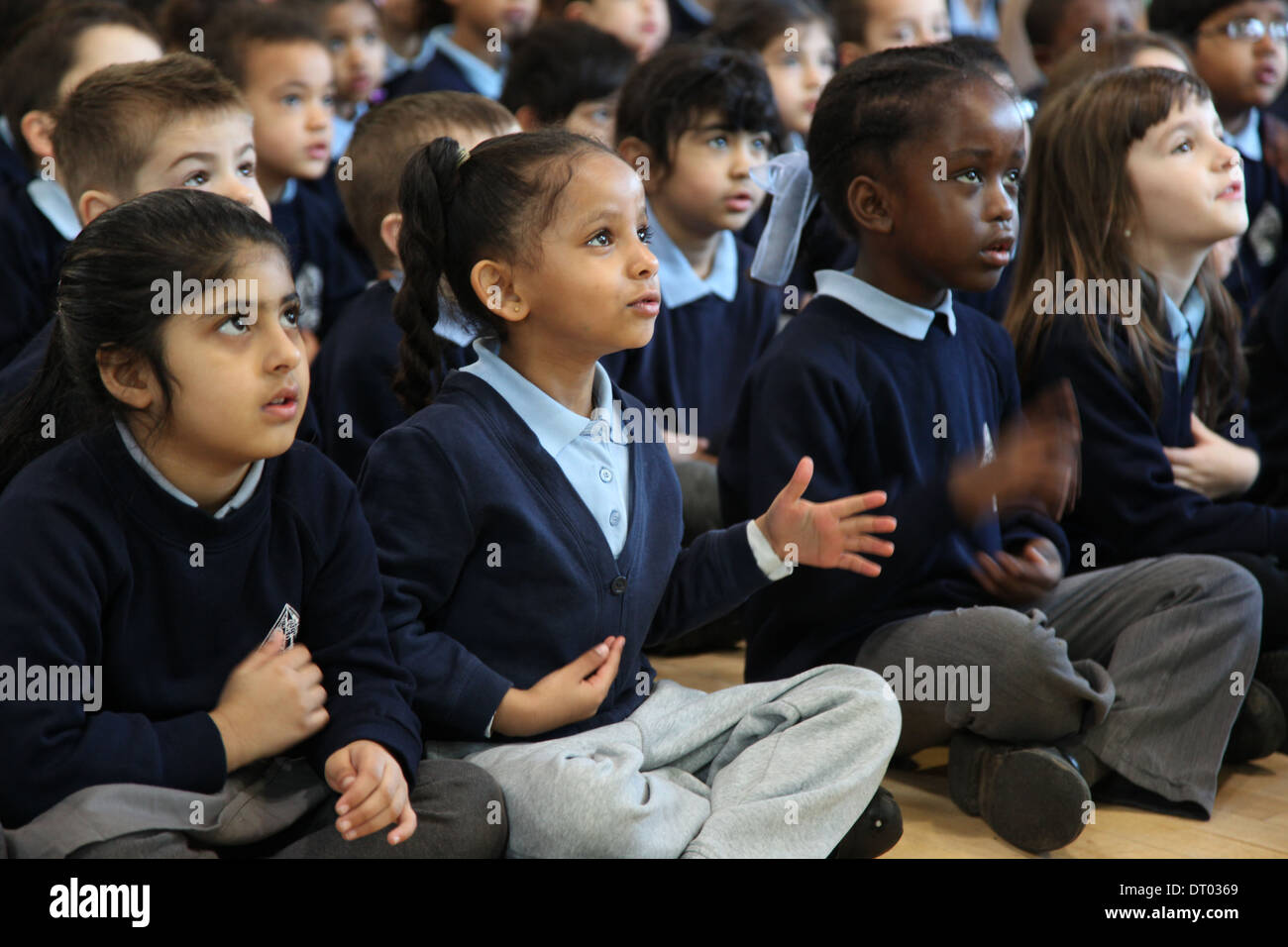 Children at a school assembly singing, clapping and performing actions - Stock Image