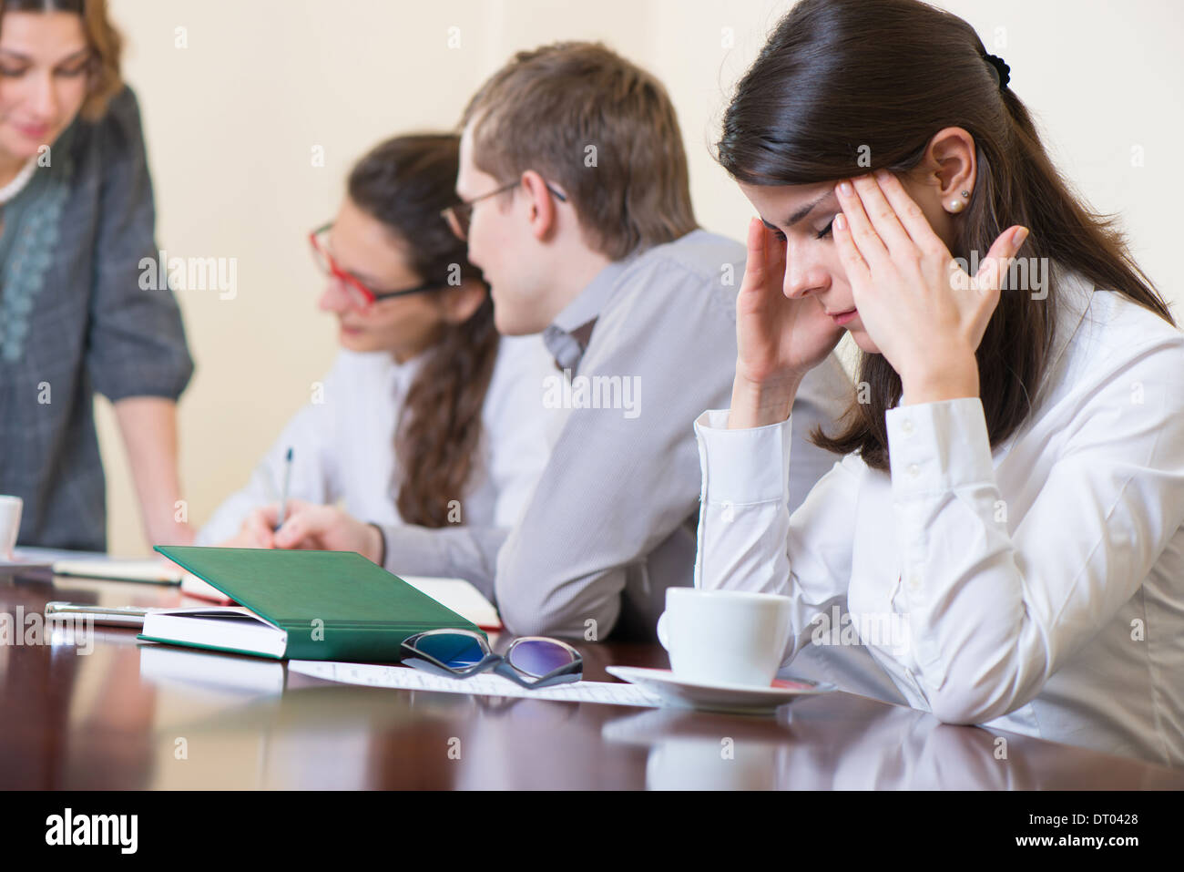 Young tired business woman with headache sitting at seminar - Stock Image
