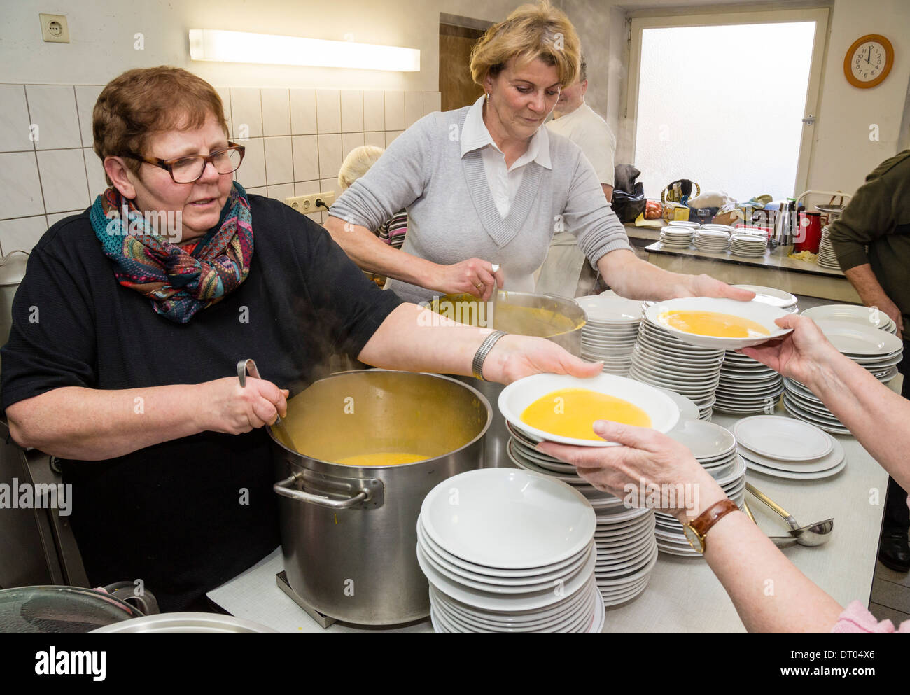 Volunteers of a local church community fill plates with pumpkin soup, which is served as a christmas dinner for homeless people - Stock Image