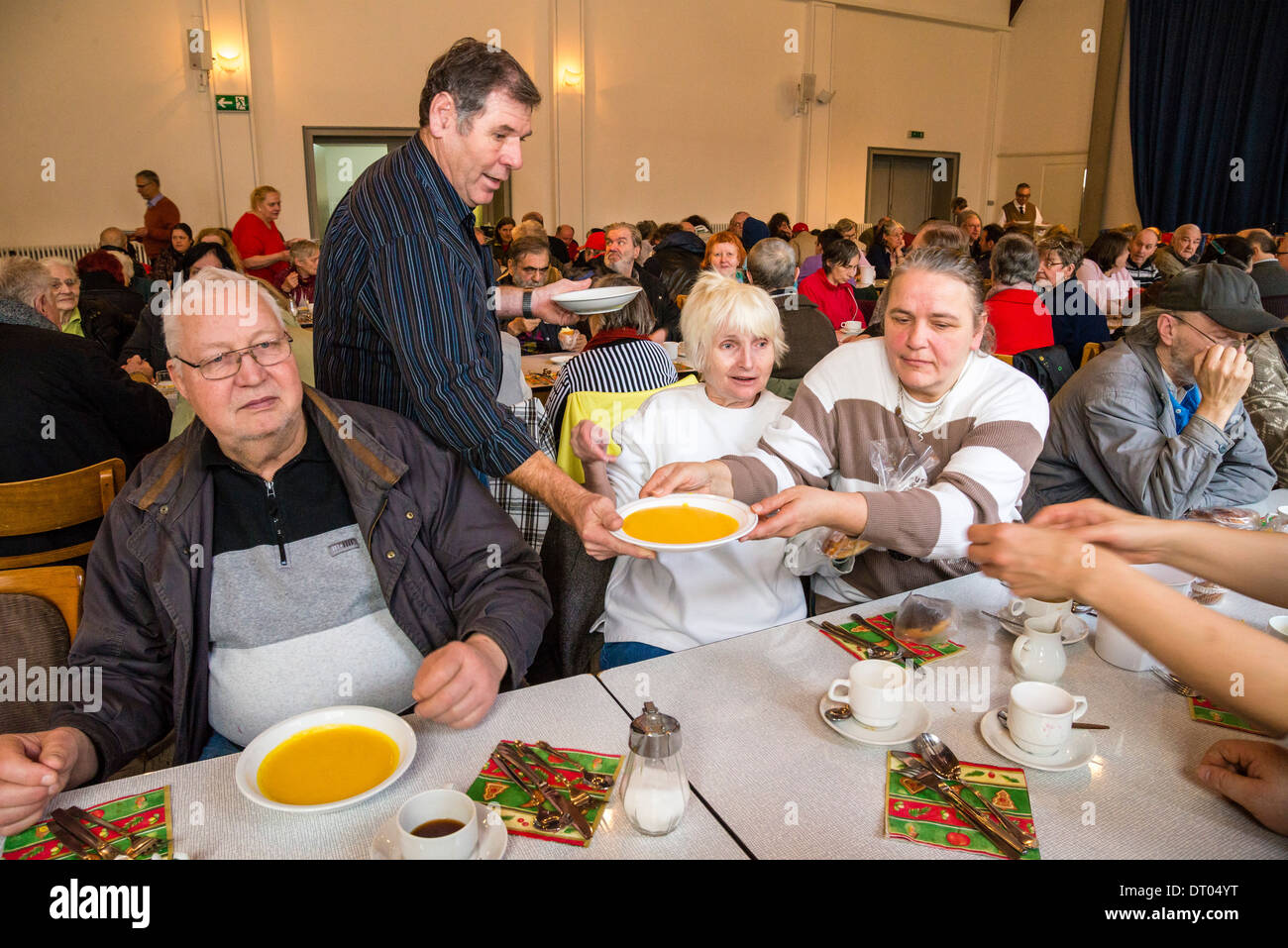 Homeless people have a christmas dinner, served by volunteers of a local church community. - Stock Image