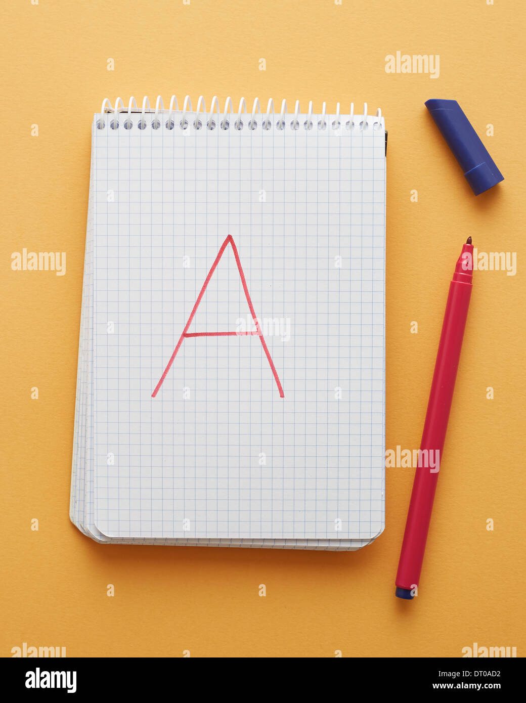 A letter handwritten in notebook page on yellow background alphabet - Stock Image